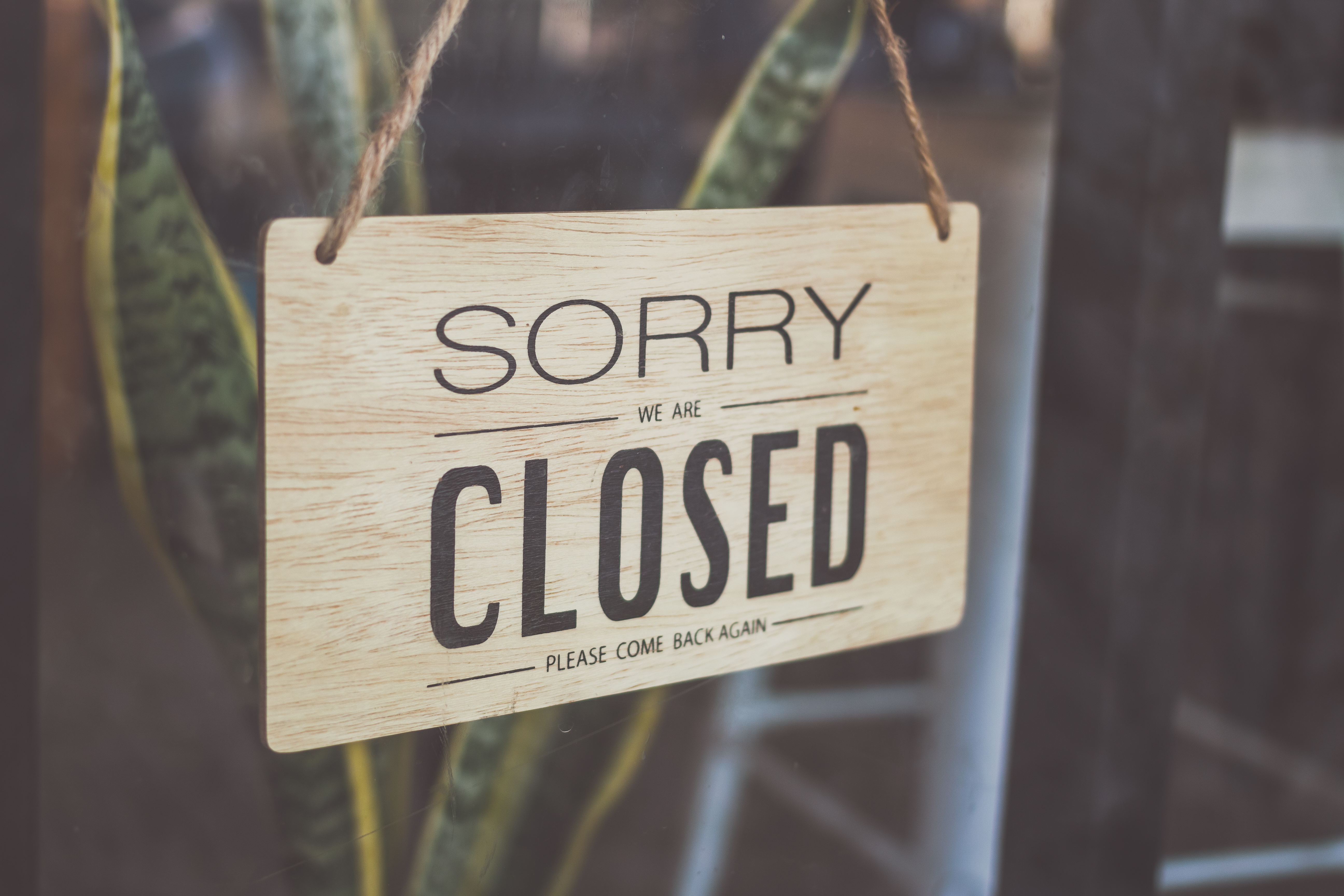 """A beige sign on a restaurant window with black lettering says """"Sorry We Are Closed Please Come Back Again,"""" with a houseplant in the background."""