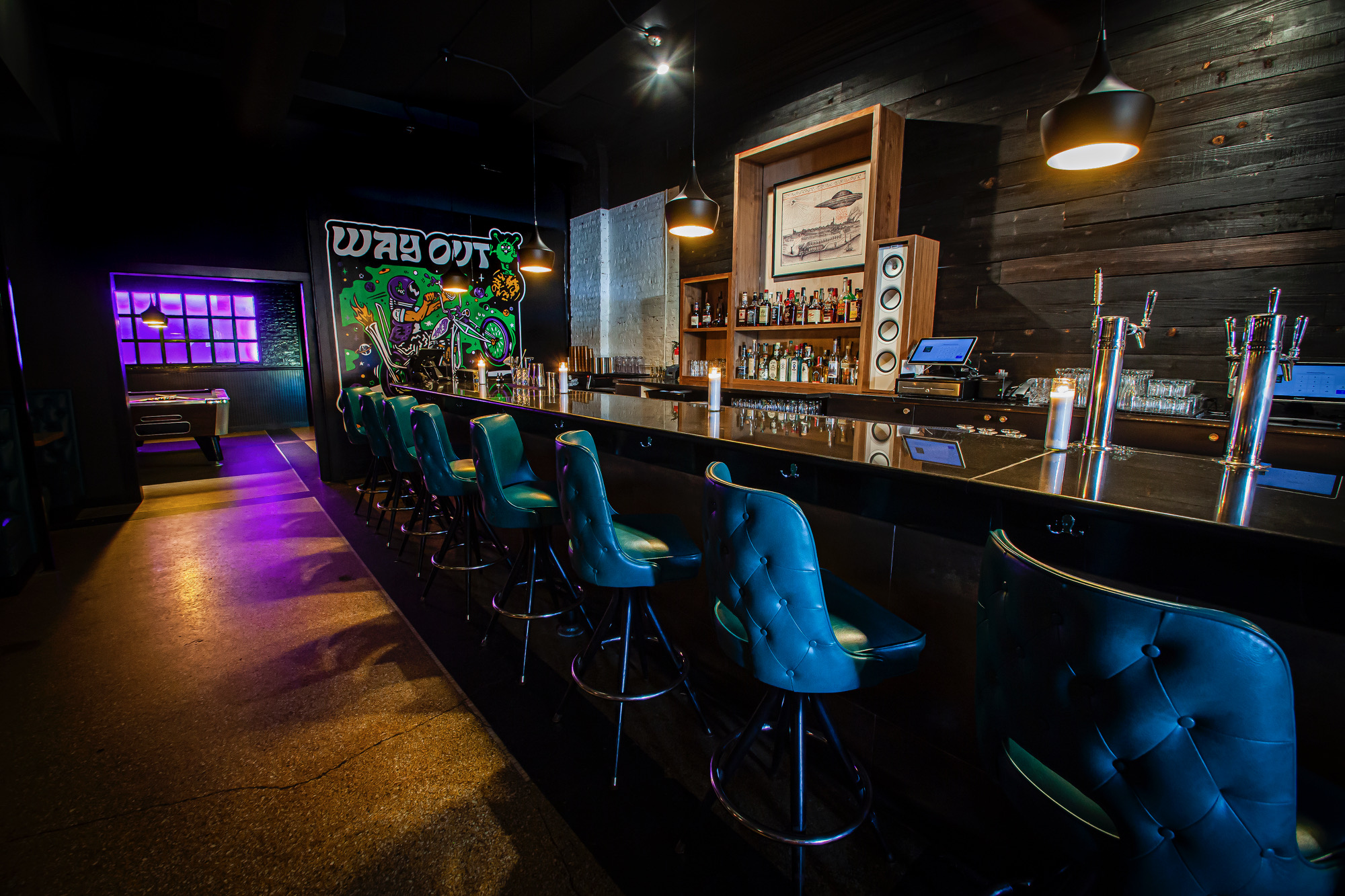 A dark bar with blue stools