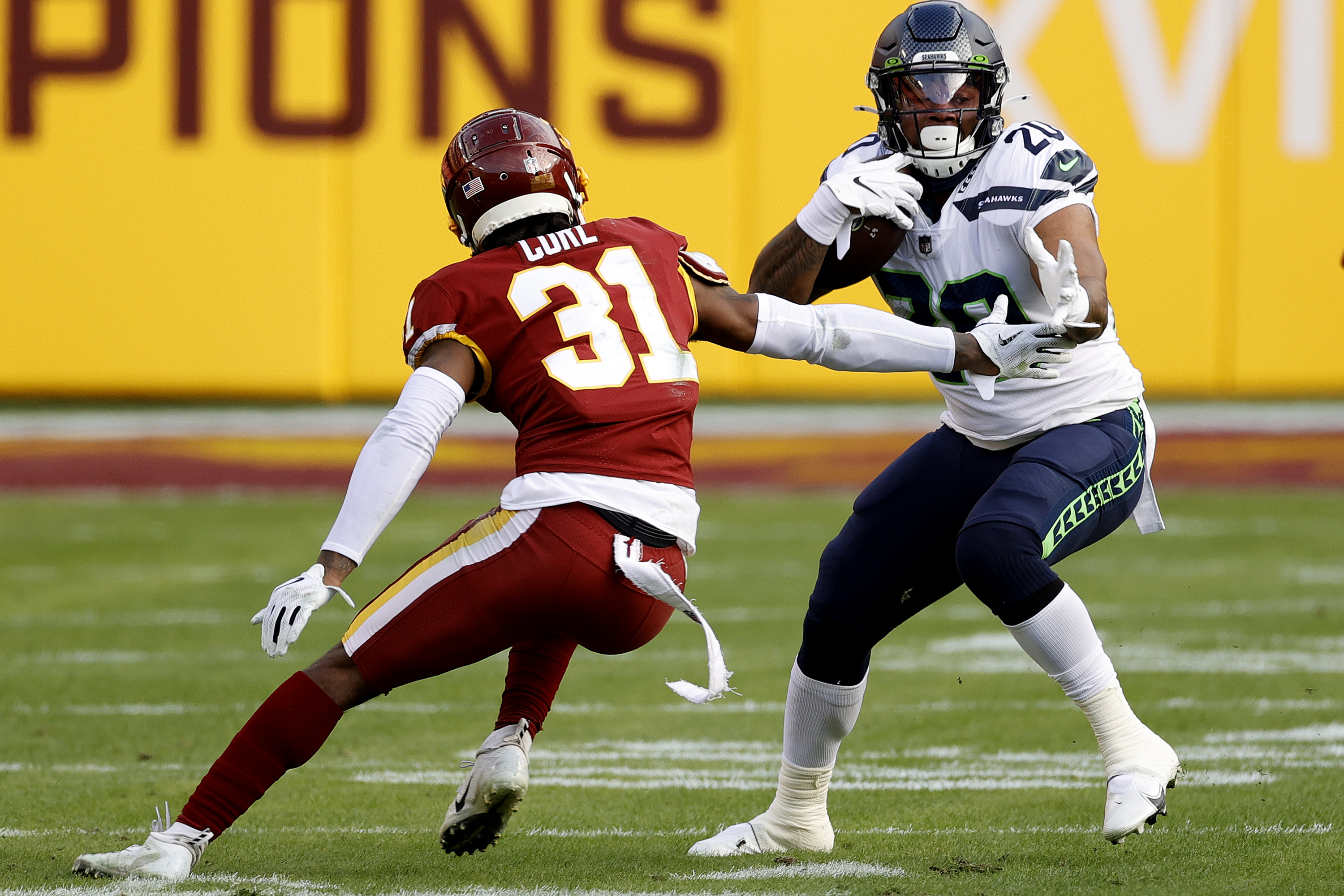 Rashaad Penny #20 of the Seattle Seahawks breaks a tackle attempt by Kamren Curl #31 of the Washington Football Team at FedExField on December 20, 2020 in Landover, Maryland.