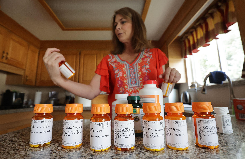 Debra Grant looks over her heart medication at her home in Salt Lake City on Aug. 8.