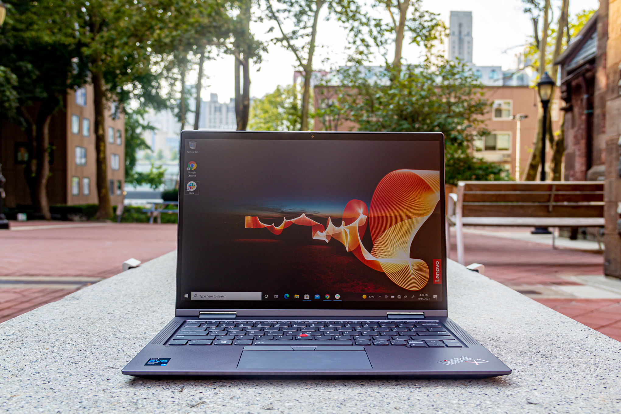 The ThinkPad X1 Yoga Gen 6 on a bench in an outdoor park, open. The screen displays an outdoor night scene with an orange banner rippling across it and the Lenovo banner on the bottom right side.