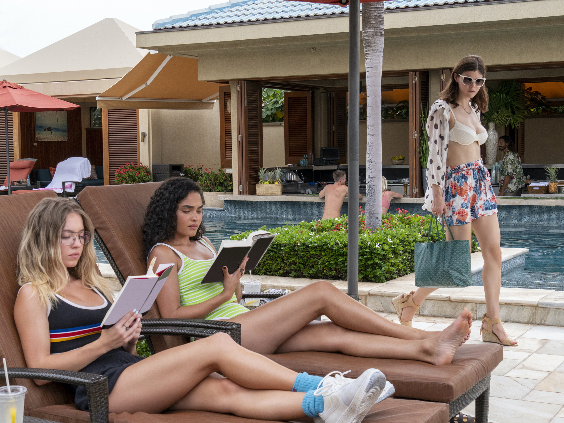 Olivia and Paula sit by the pool reading, as Rachel passes them in a bikini.