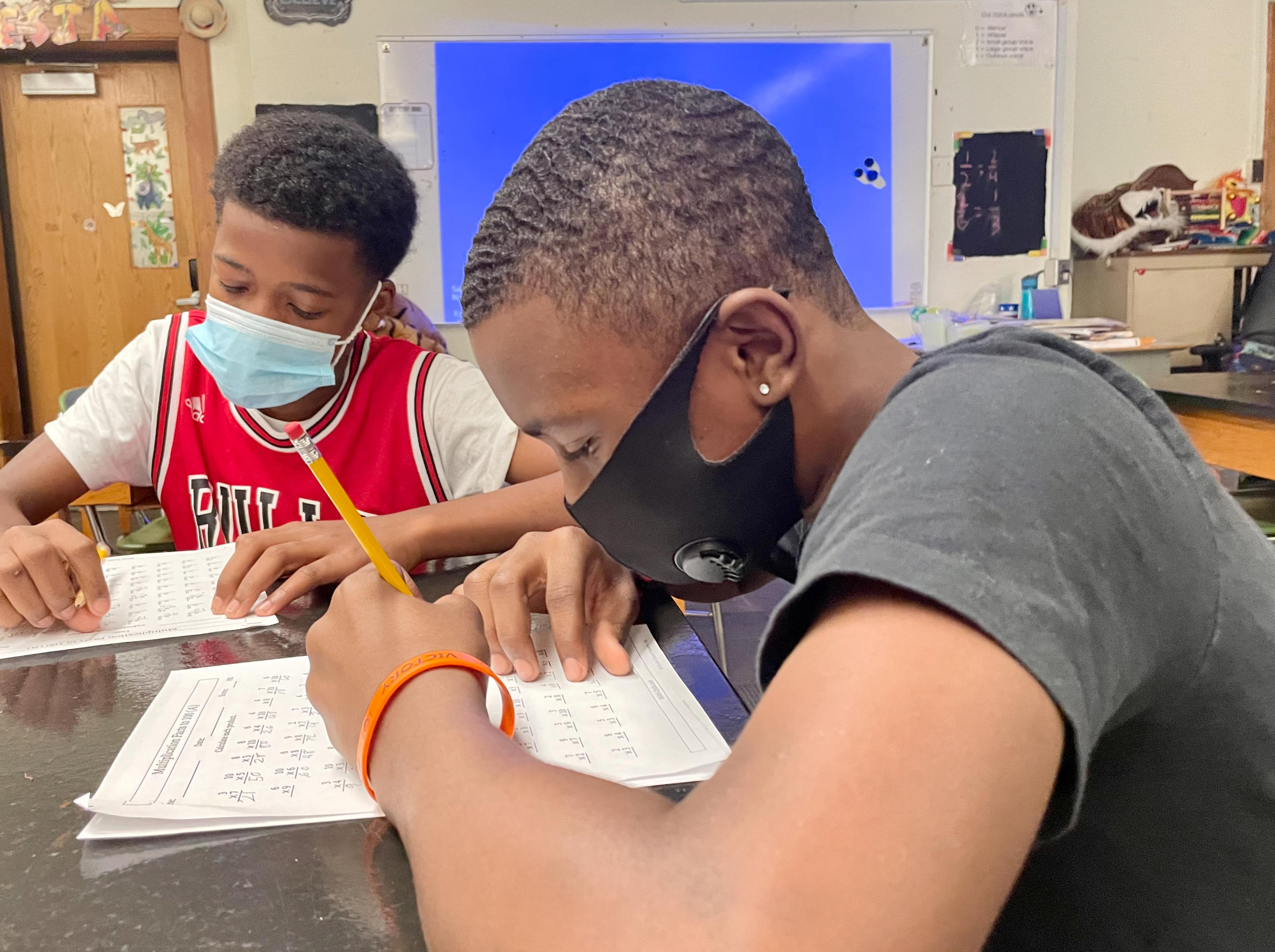 Two male middle school students work on mathematics worksheets at their desk.