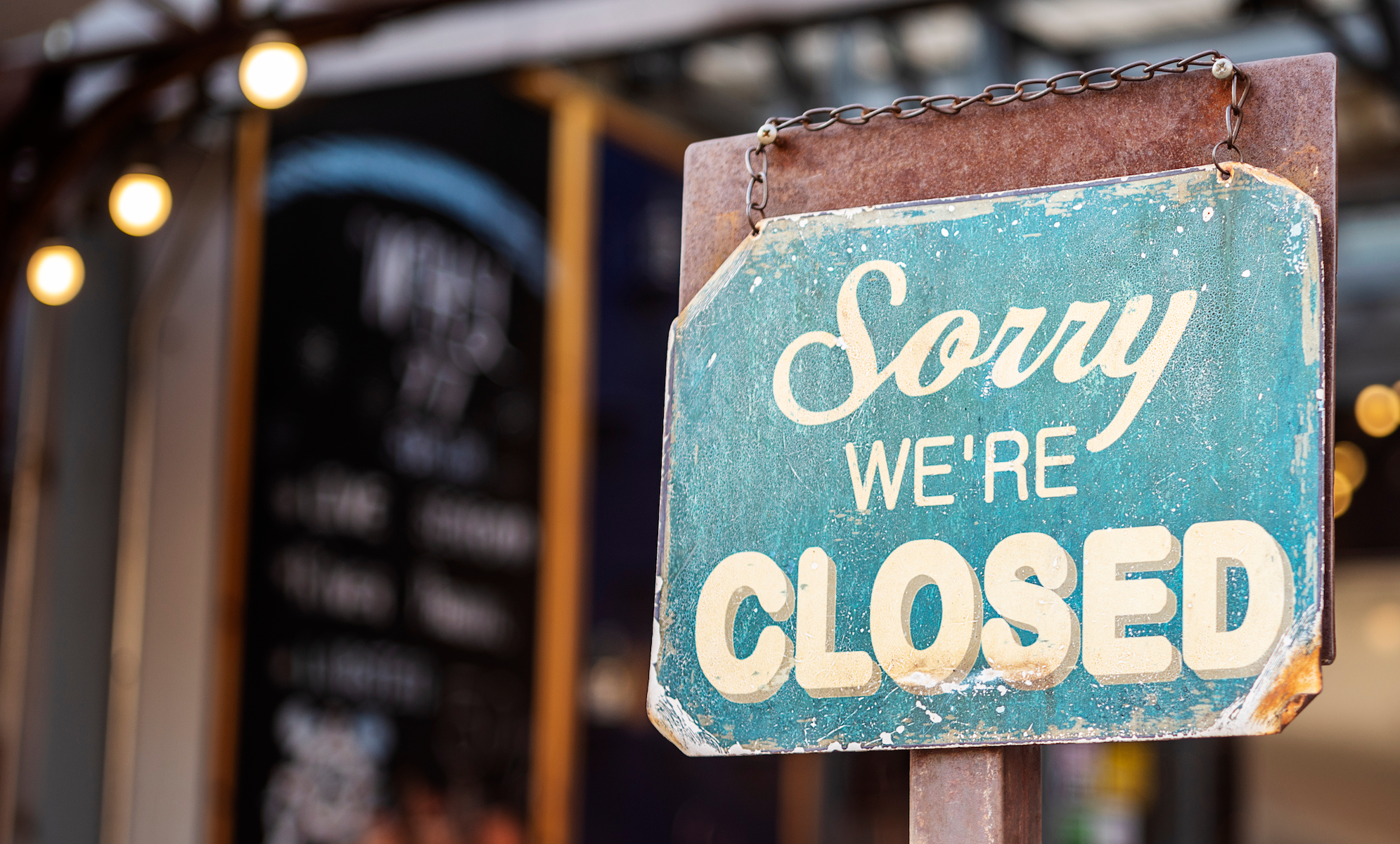"""A blue sign that reads """"Sorry, we're closed"""" hangs in a restaurant window."""