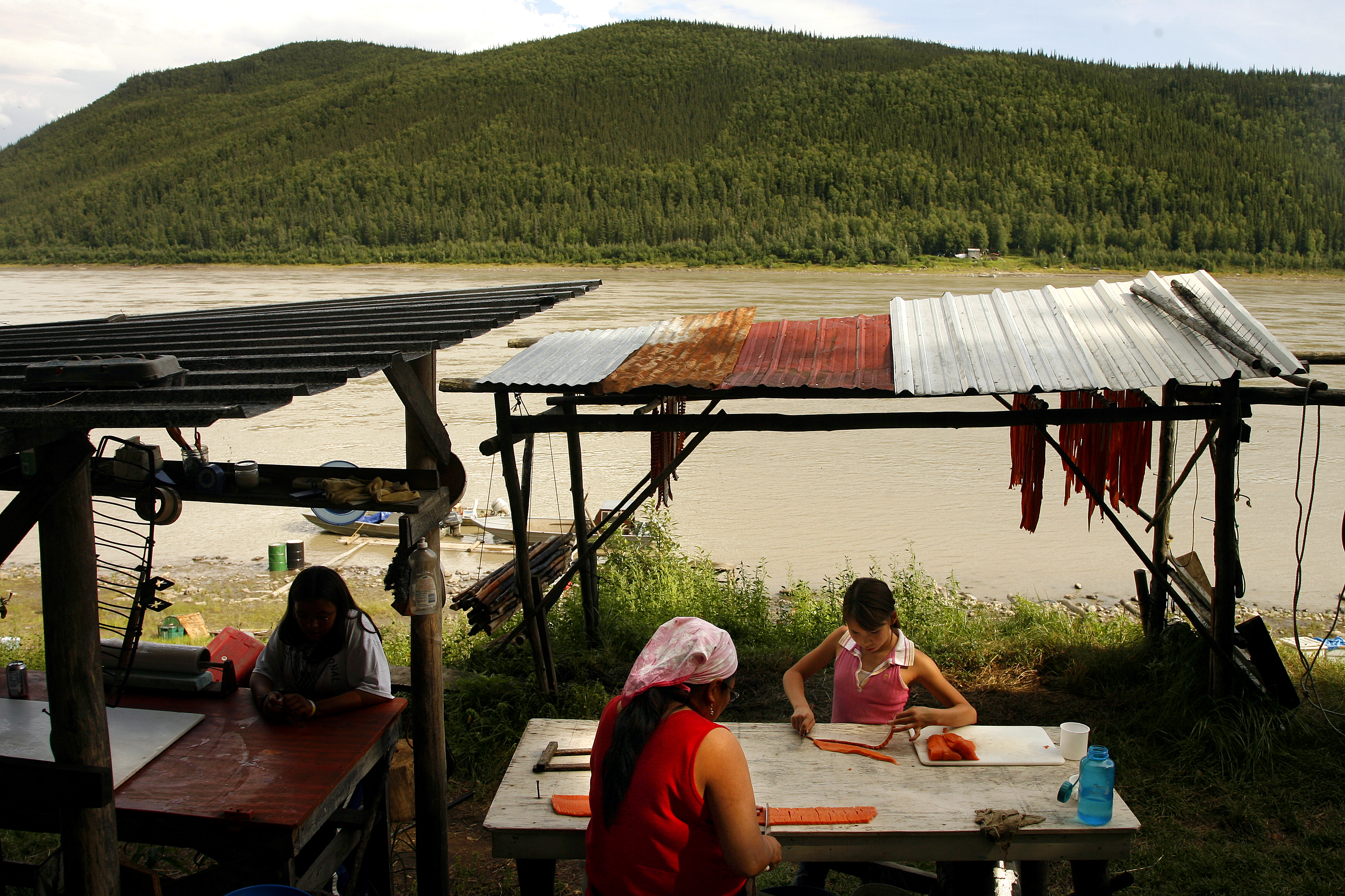Two figures sit at a picnic table under a roof where salmon filets are drying.
