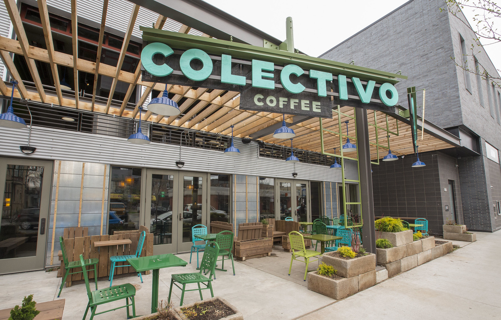 """Outdoor seating beside a large, industrial-style cafe with a large teal sign that reads """"Colectivo Coffee"""""""