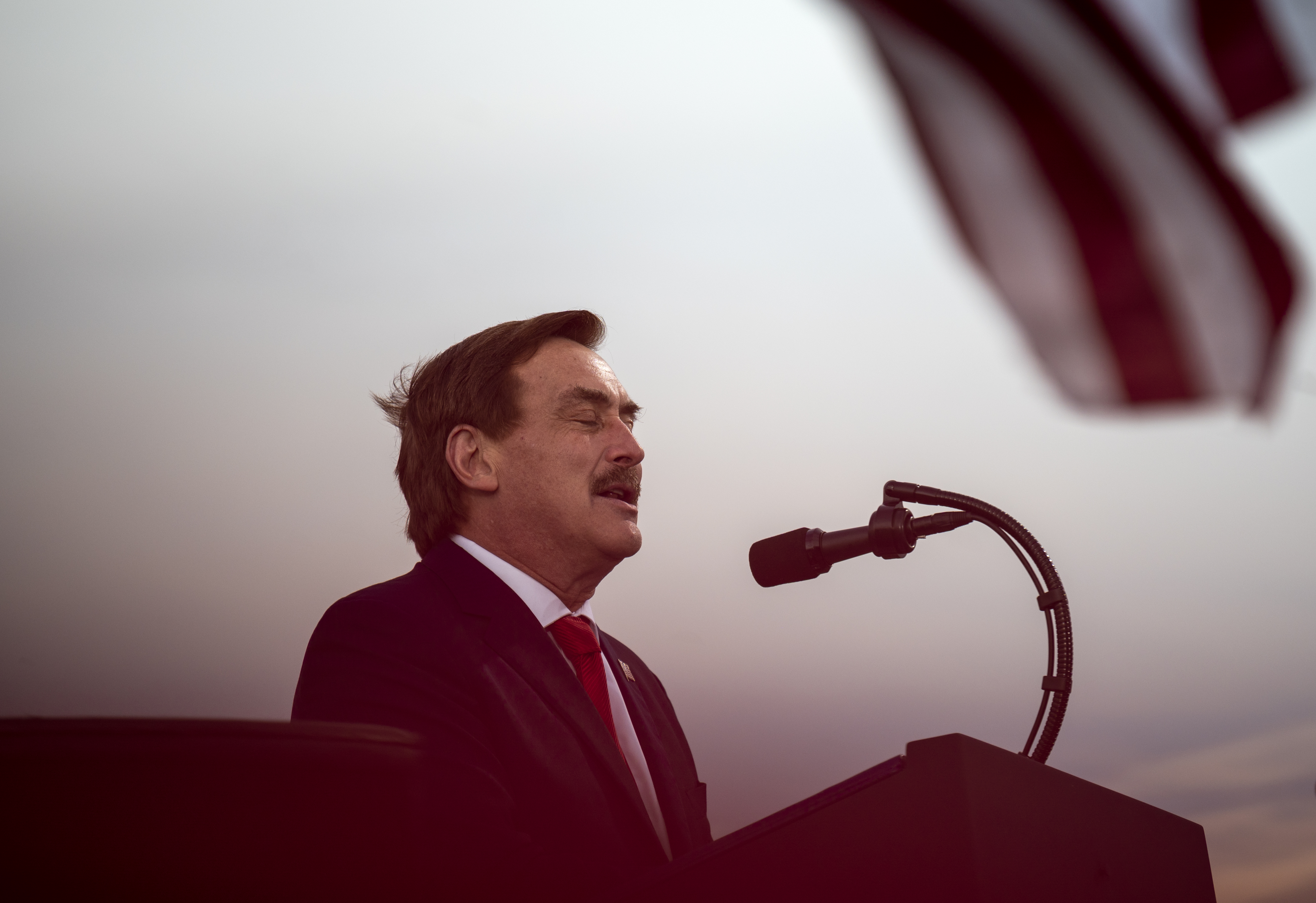 Mike Lindell's eyes are closed while he stands outdoor at a lectern against a twilight sky