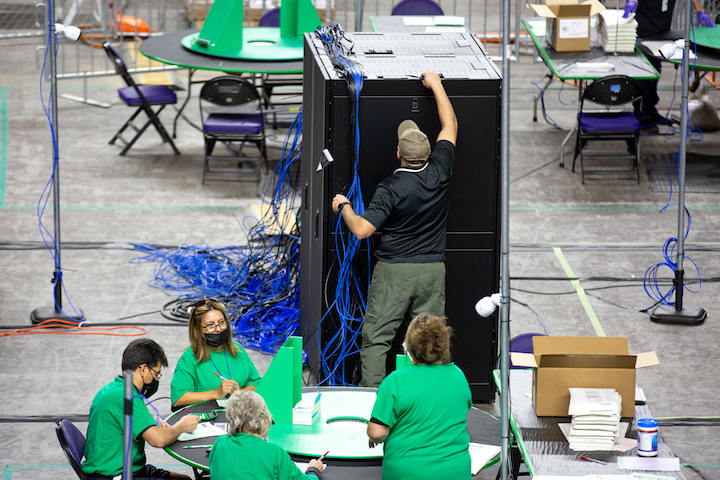 Four workers in green T-shirts seated at a round table on the floor of an arena. One man standing before a tall stack of computer servers reaches to the top of the equipment.
