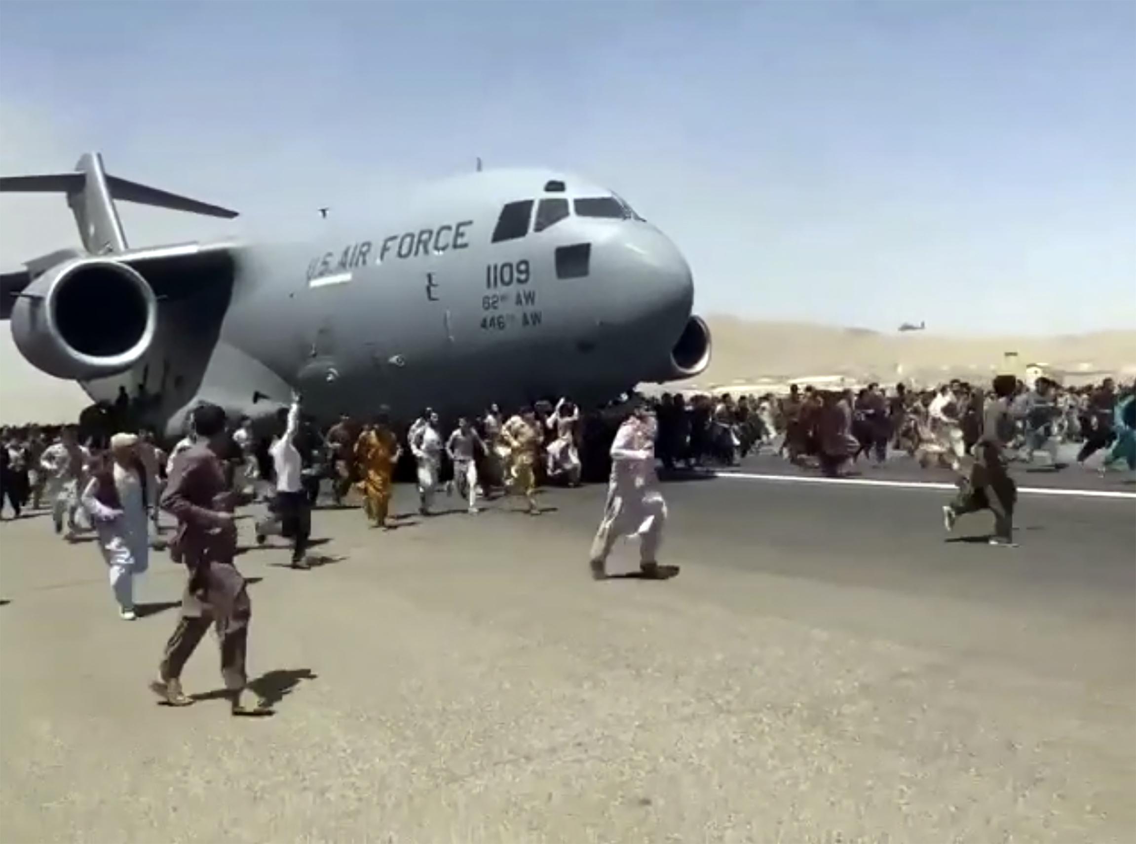 Afghans run alongside a U.S. Air Force plane as it leaves Kabul, Afghanistan