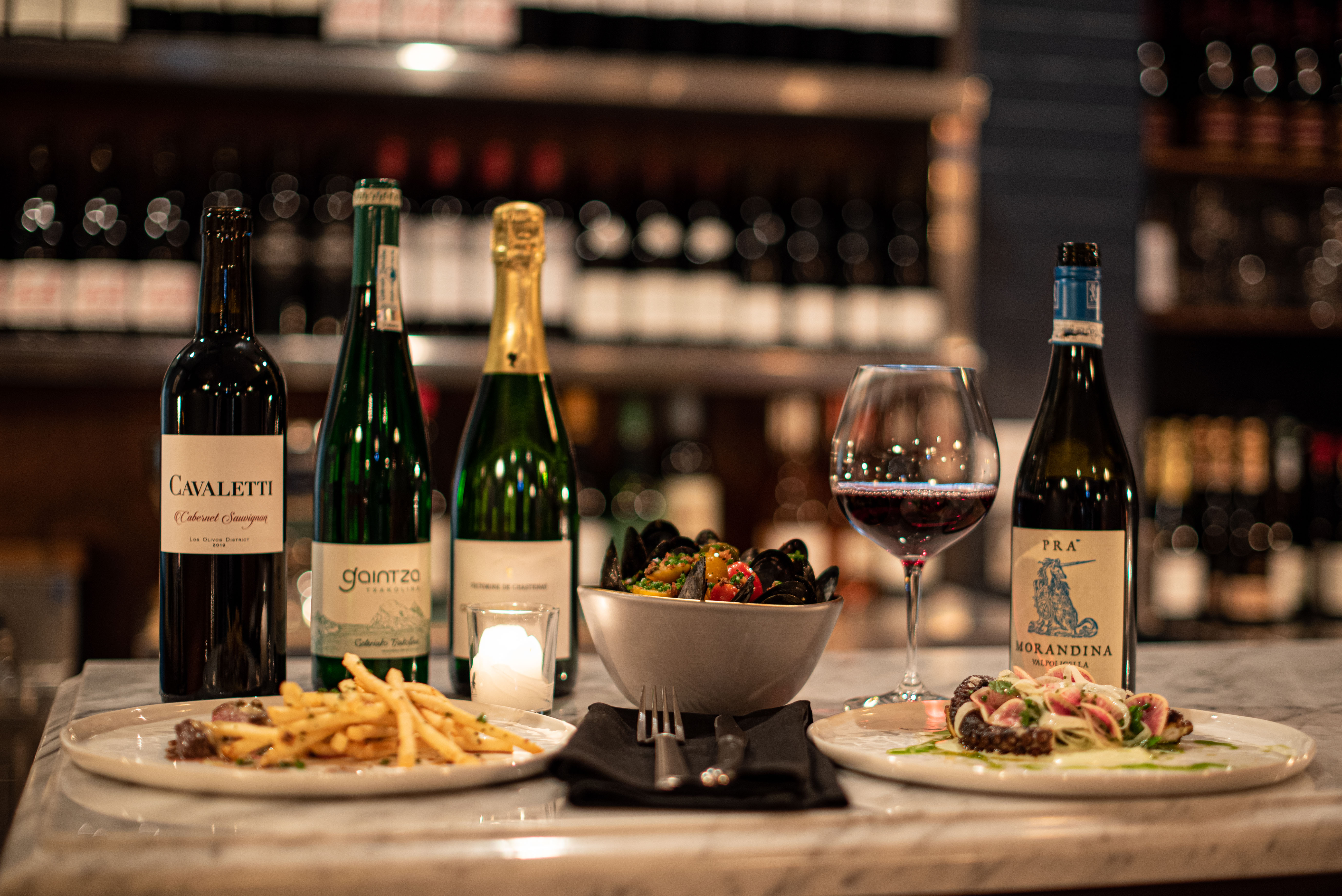 Bottles of wine and small plates Italian and French food on a marble countertop.