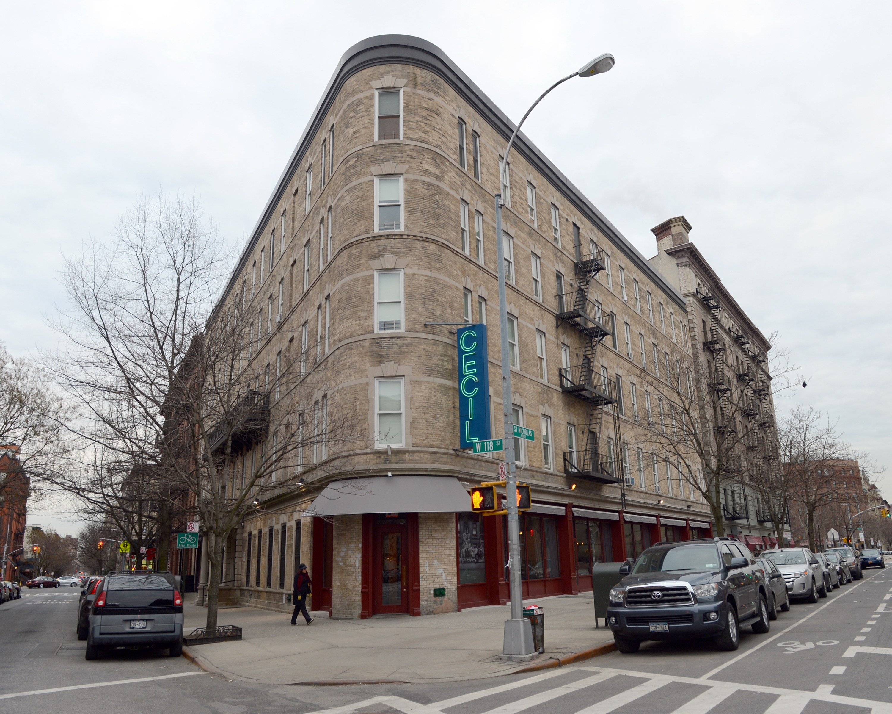 """A curved brown building in a residential area boasts a blue sign with neon lettering that reads """"Cecil"""""""