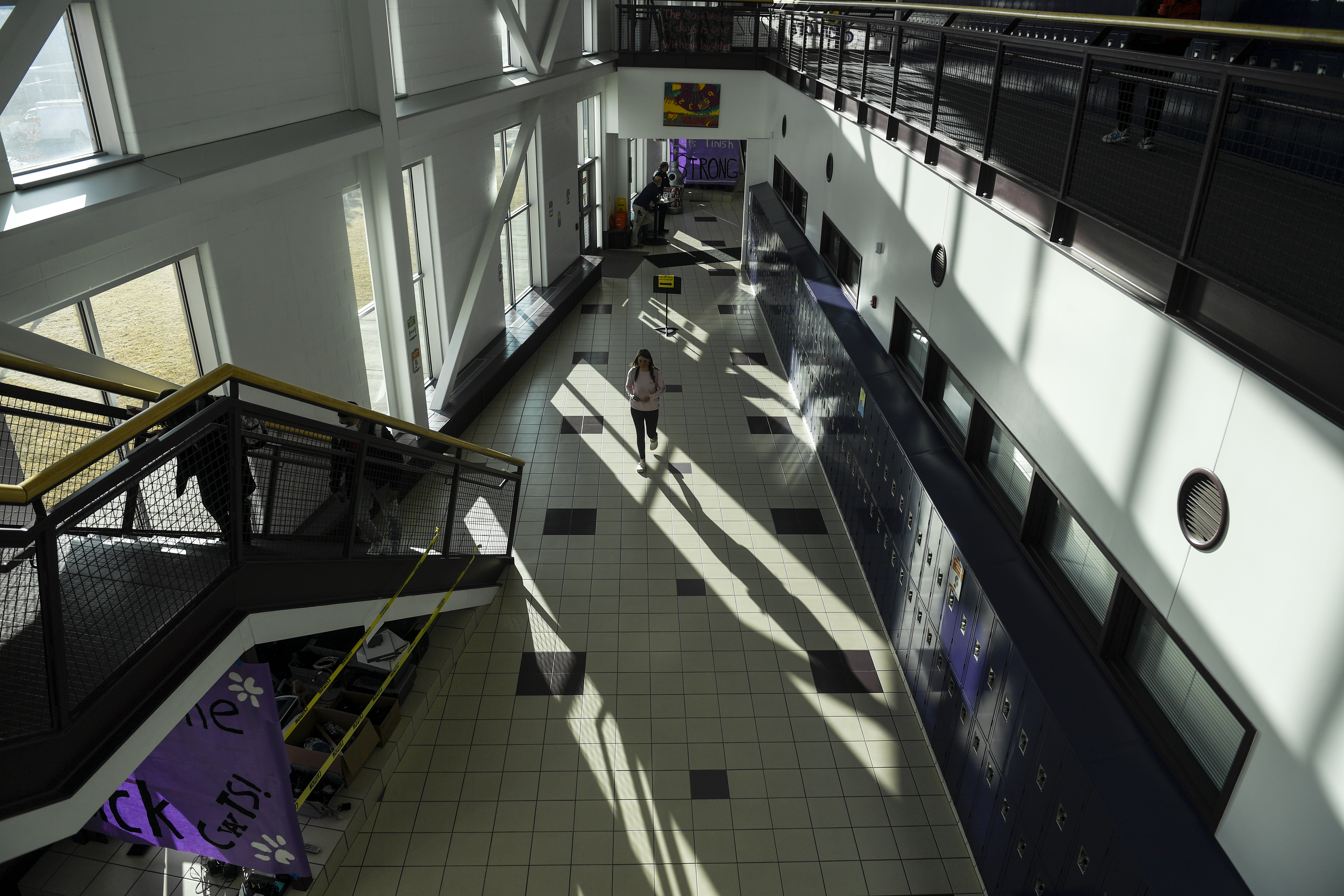 Seen from above, a masked student walks in a wide school corridor.