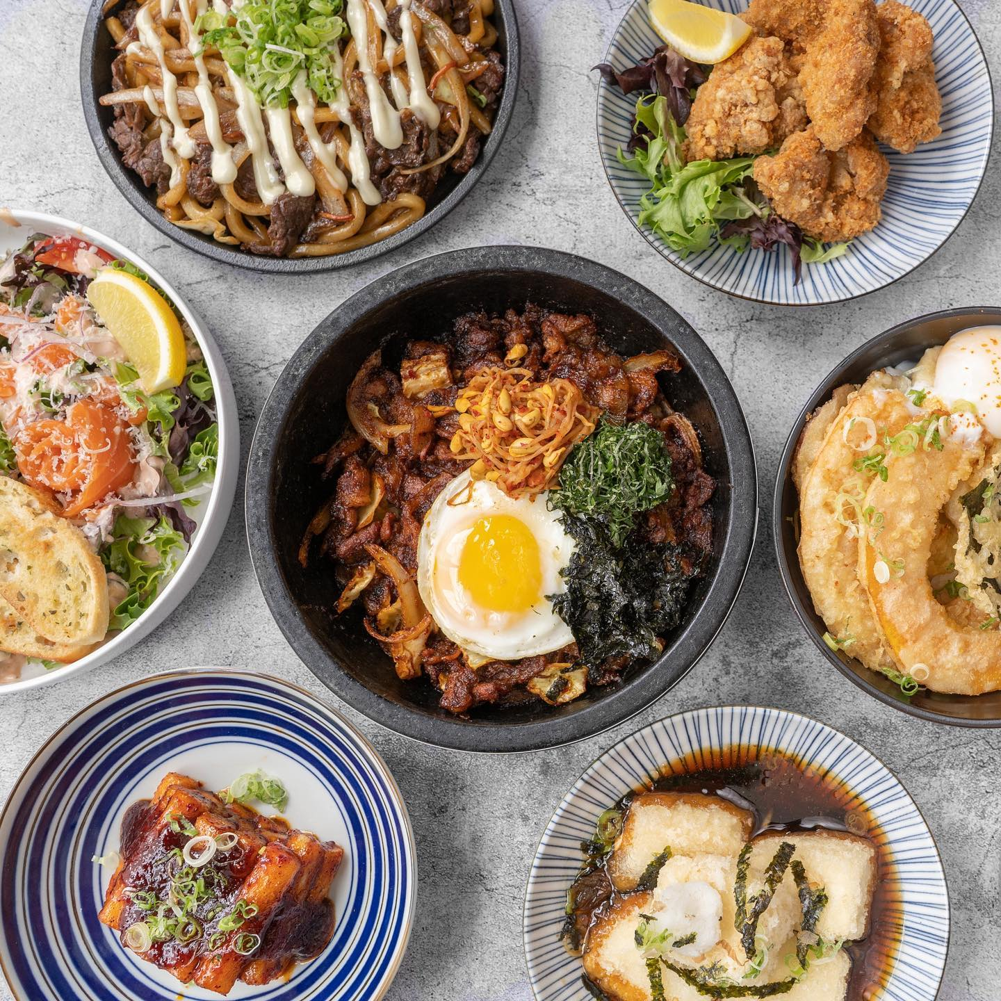 concrete table covered in korean and japanese food