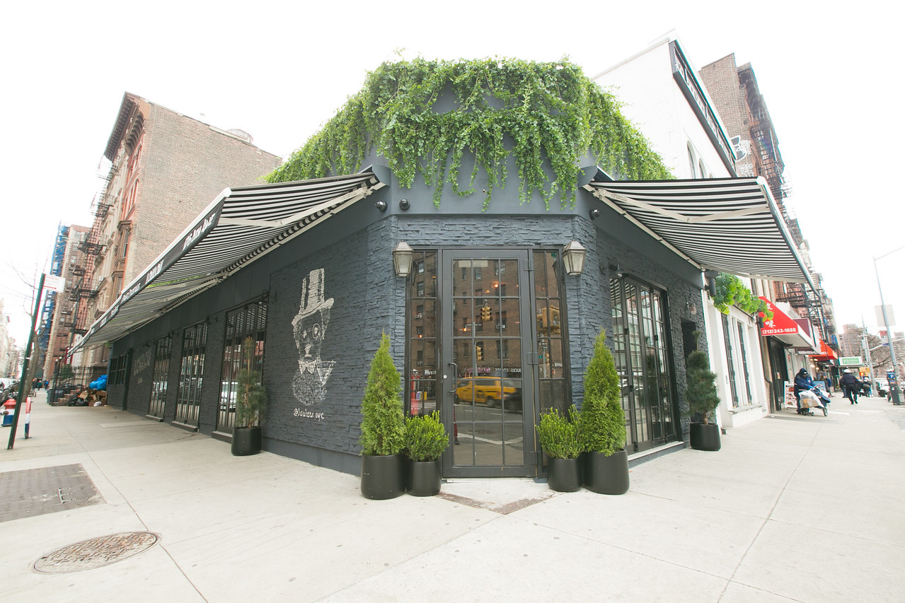A grey restaurant corner facade with dark awnings draped with green ivy.
