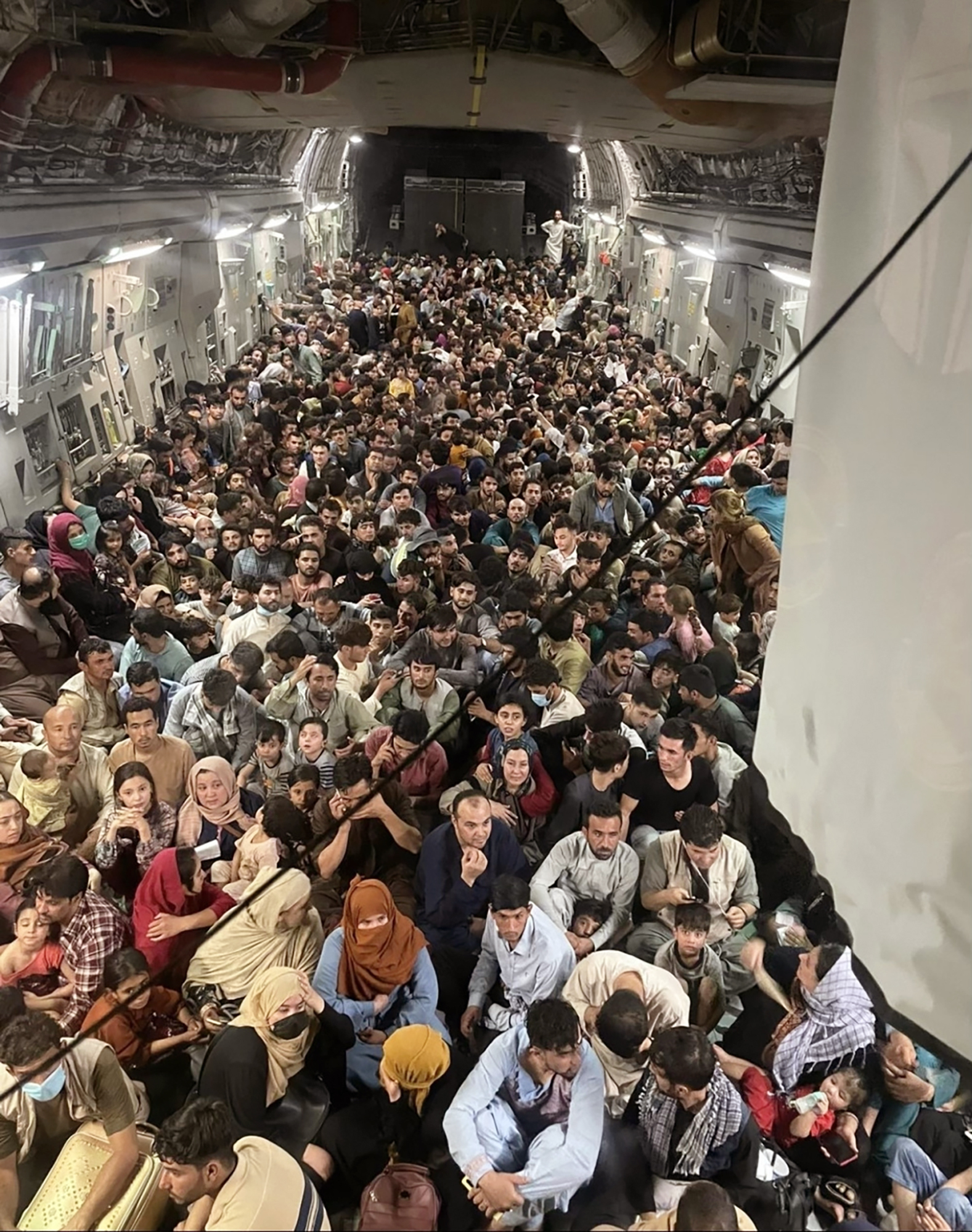 Afghan citizens pack inside a U.S. Air Force plane as they are transported from Hamid Karzai International Airport in Afghanistan.