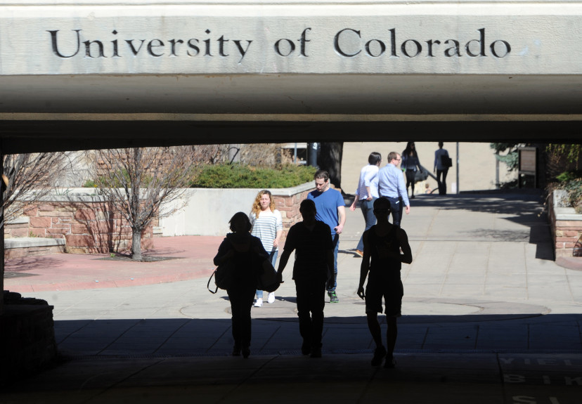 """Several people walk underneath a grey bridge with the words """"University of Colorado"""" etched into the concrete."""