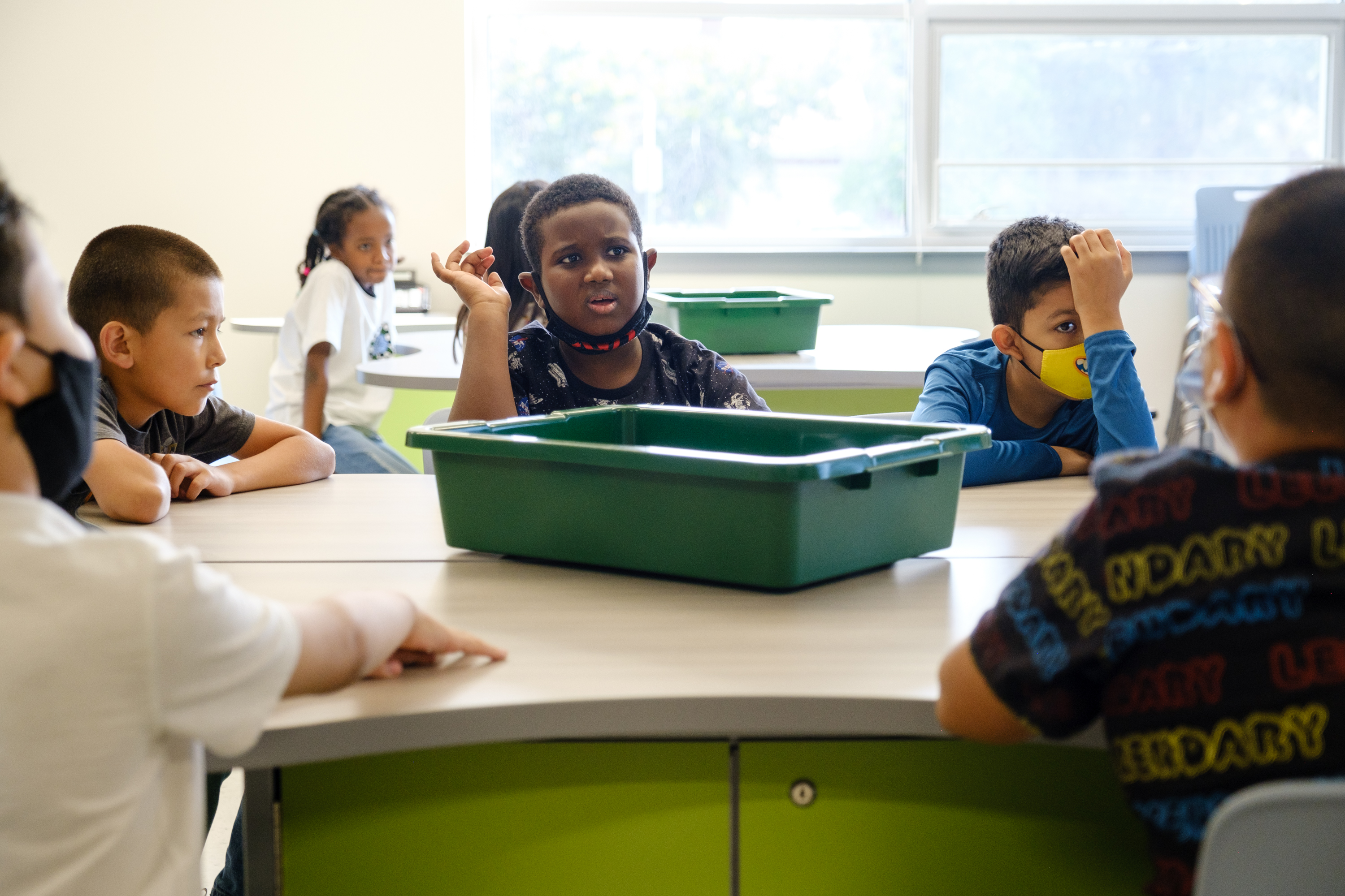 Students with and without masks sit around a table with a green plastic bin in the middle of the table.