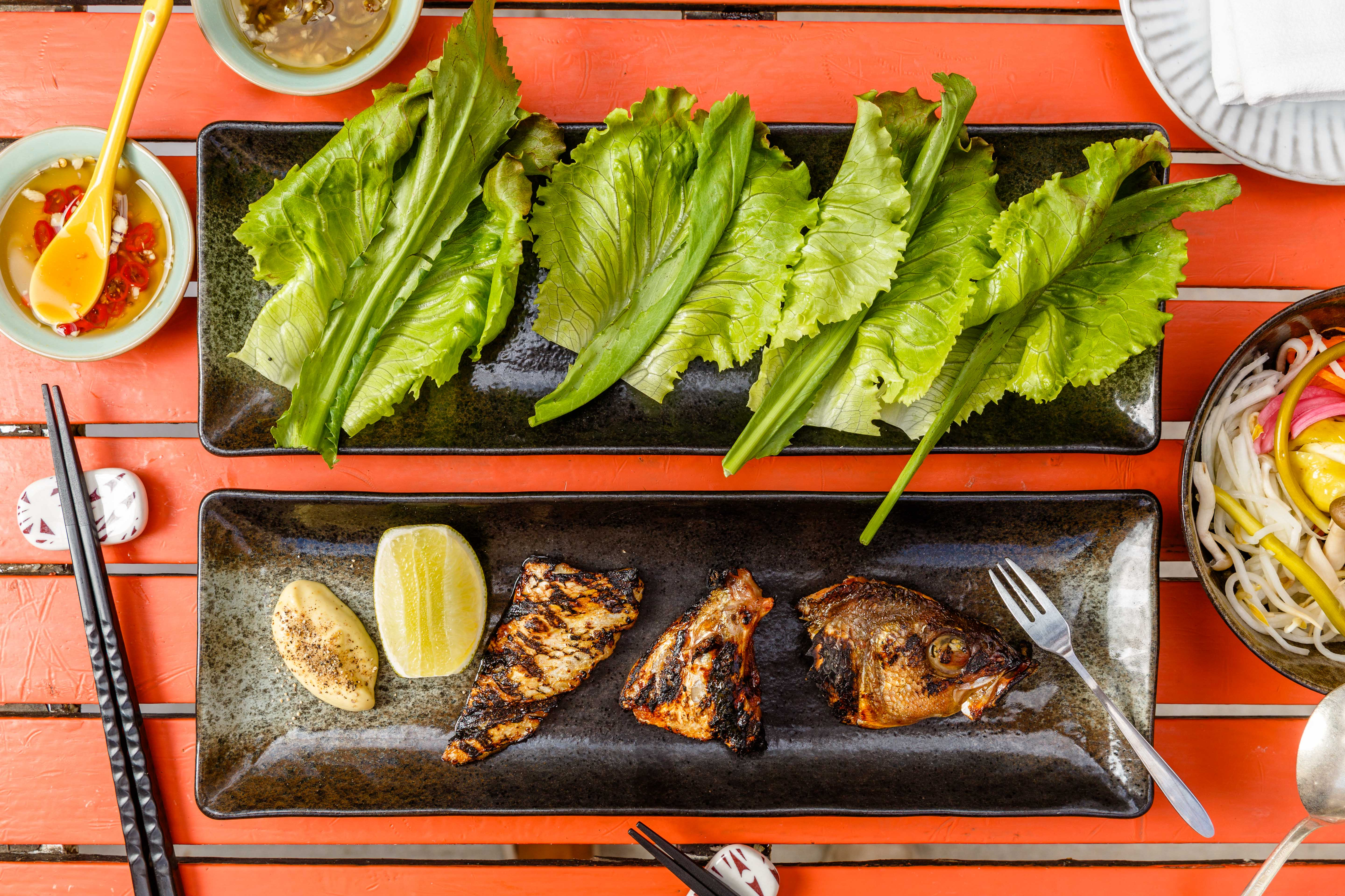 Fish head, collar, and belly sits on a plate next to a separate dish of lettuce leaves