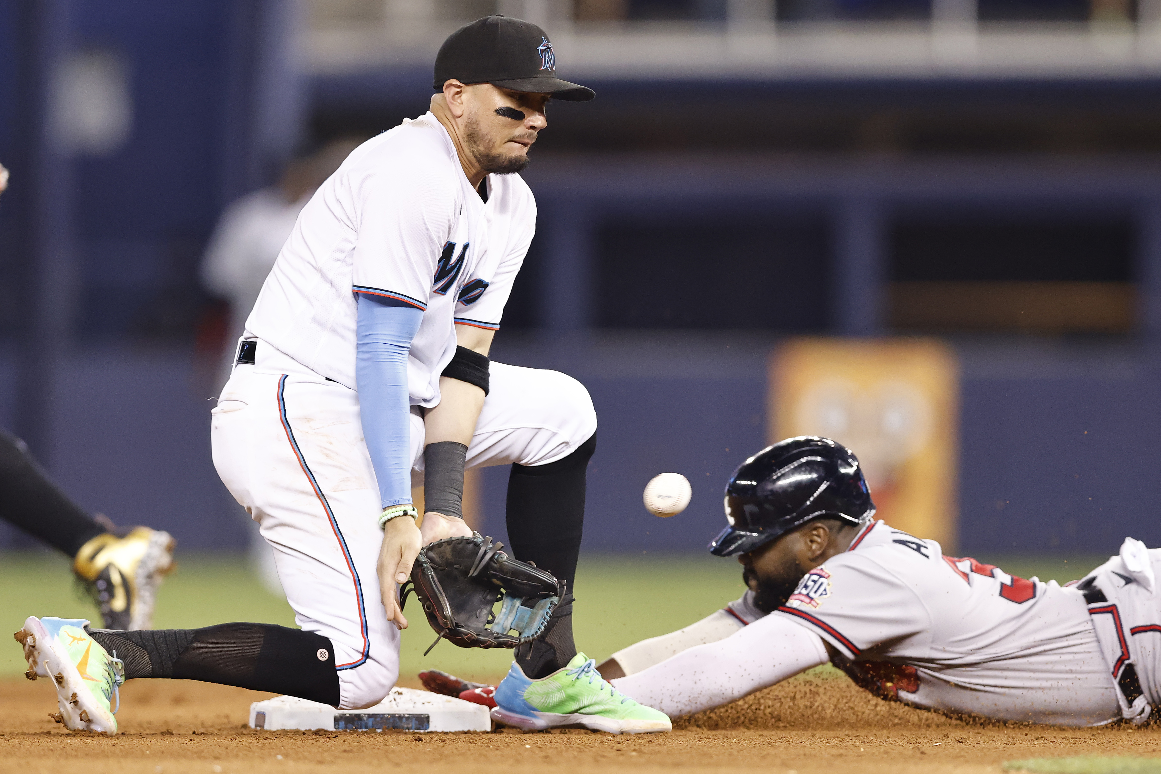 Abraham Almonte #34 of the Atlanta Braves slides safely past the tag of Miguel Rojas #19 of the Miami Marlins after stealing second base during the eighth inning at loanDepot park