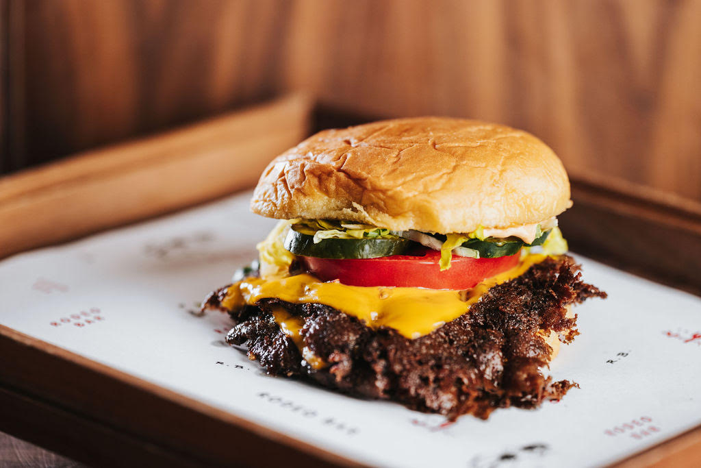 a smashburger with melted cheese, tomatoes and pickles