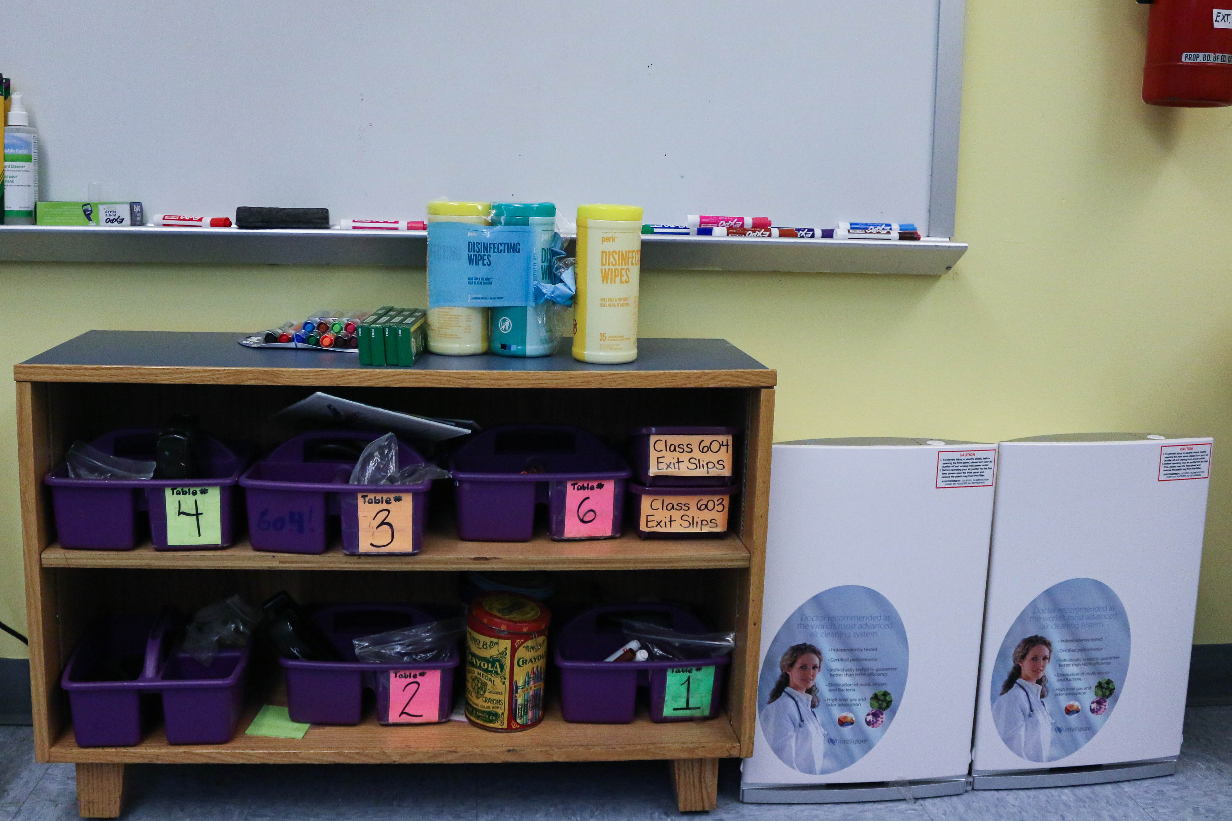 Two Intellipure air purifiers sit next to a storage shelf and a whiteboard in a New York City classroom.