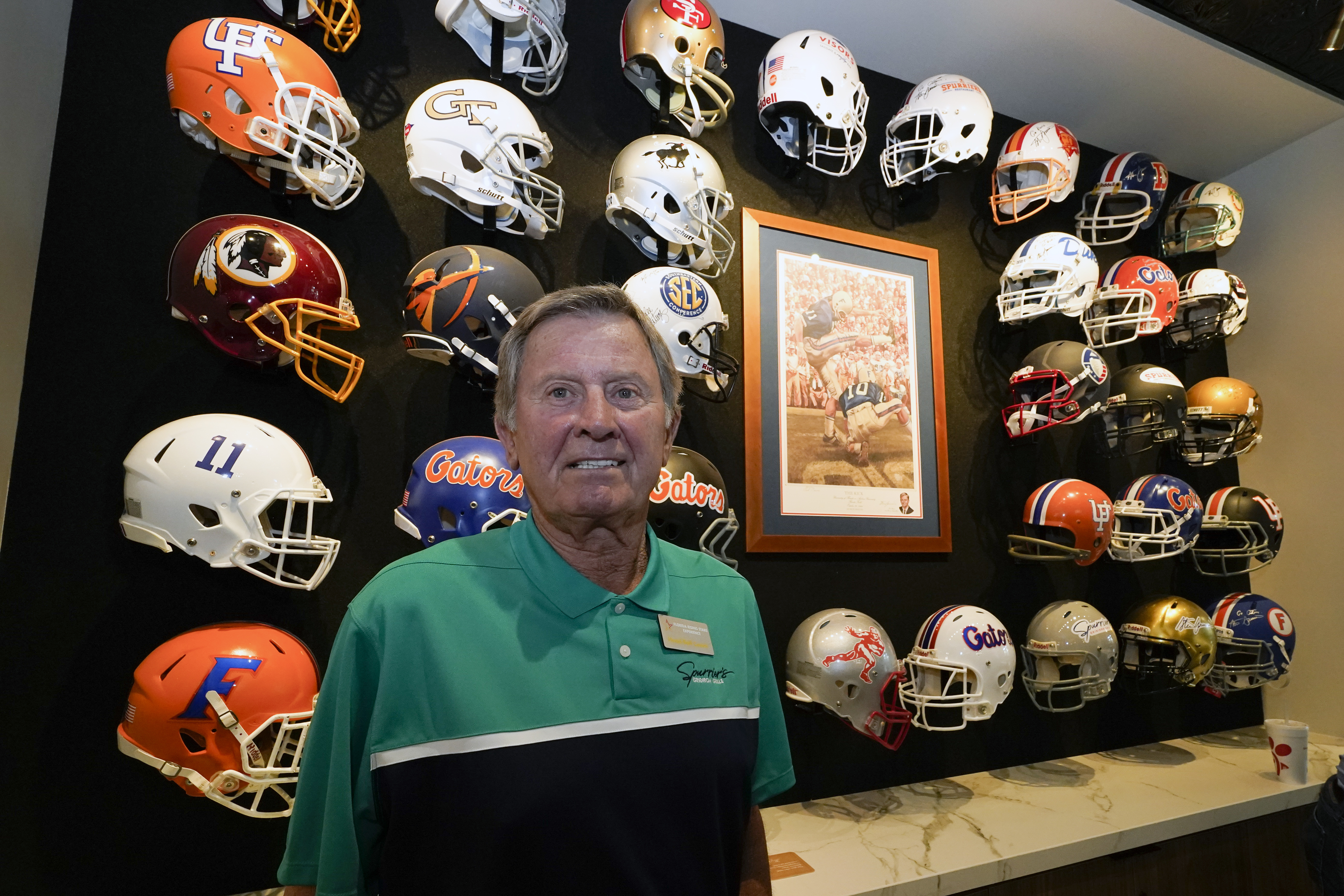 Steve Spurrier stands in front of a display of helmets of teams that he previously played for or coached at his new restaurant, the Gridiron Grill, in Gainesville, Florida. The restaurant doubles as Spurrier's personal museum.
