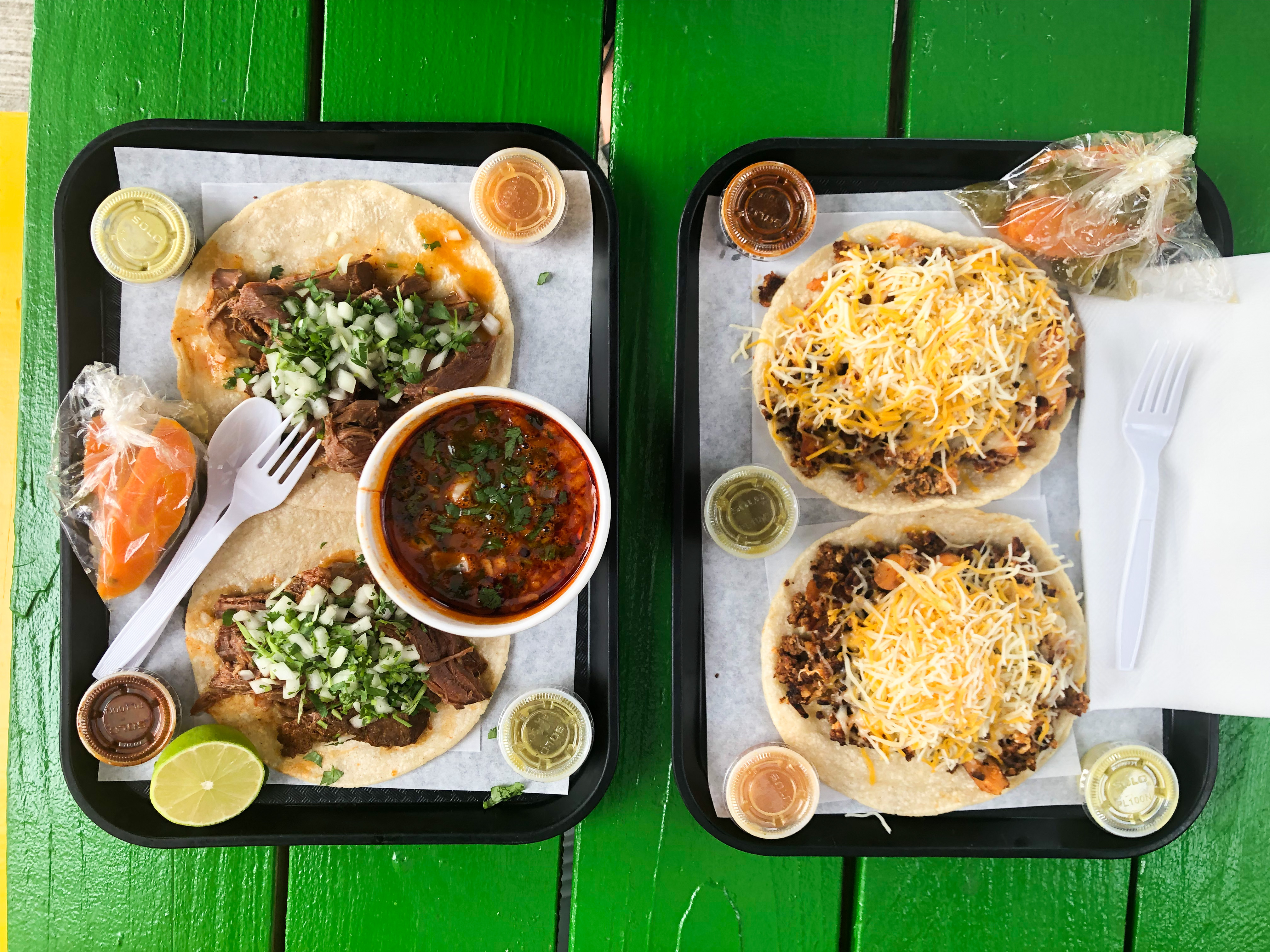 Two birria de chivo tacos sit on a plate next to an AM PM cup of consomme, next to a tray of chorizo con papas tacos with shredded cheddar. The tacos are from Sahuayo Taqueria in Portland, Oregon