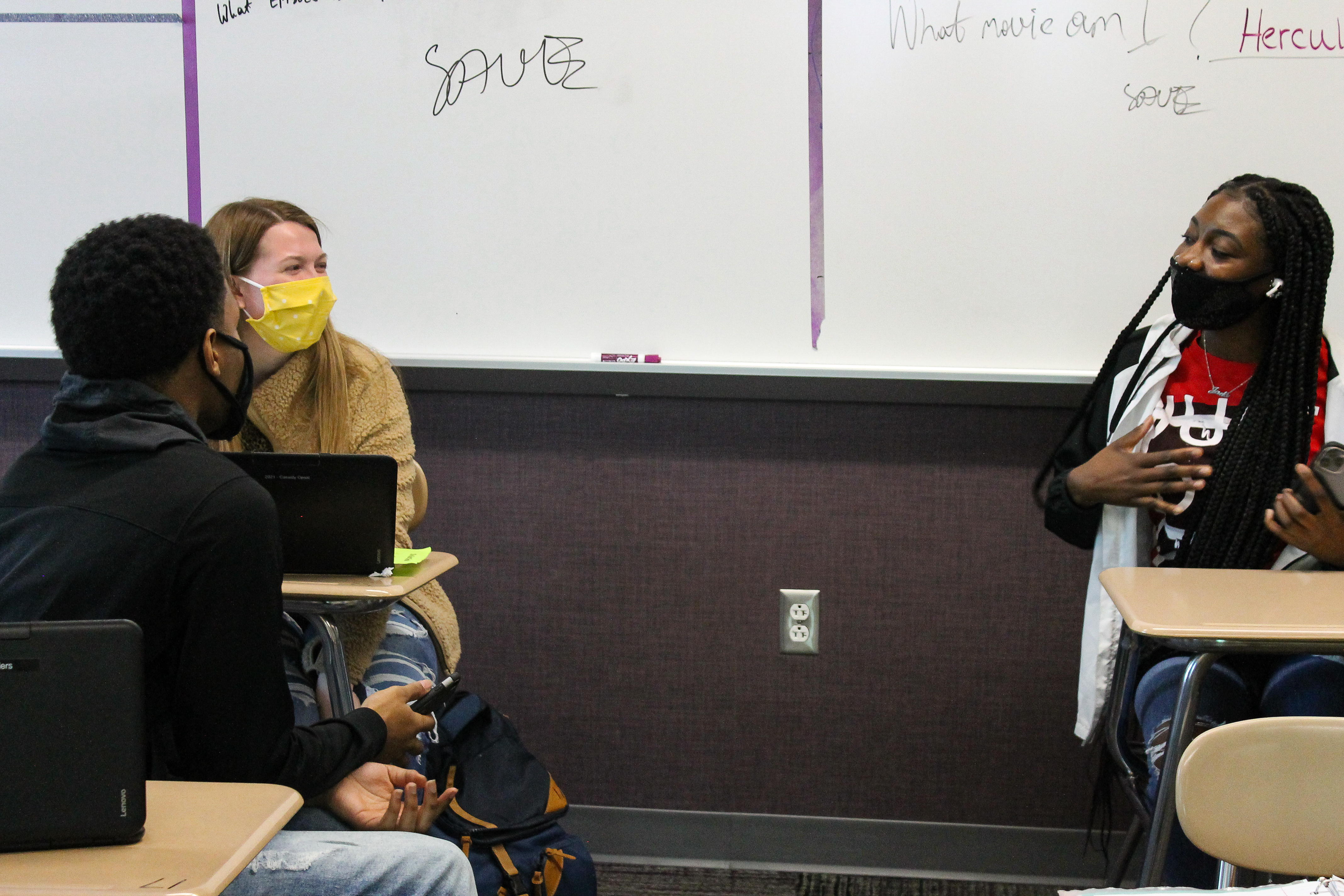 In front of a classroom white board, a student in a yellow sweater wearing a bright yellow mask sits next to a student in a black sweatshirt with a black mask. They are talking to another student seated in a desk several feet away with a red shirt and a black face mask holding her hand to her chest in the middle of speaking.