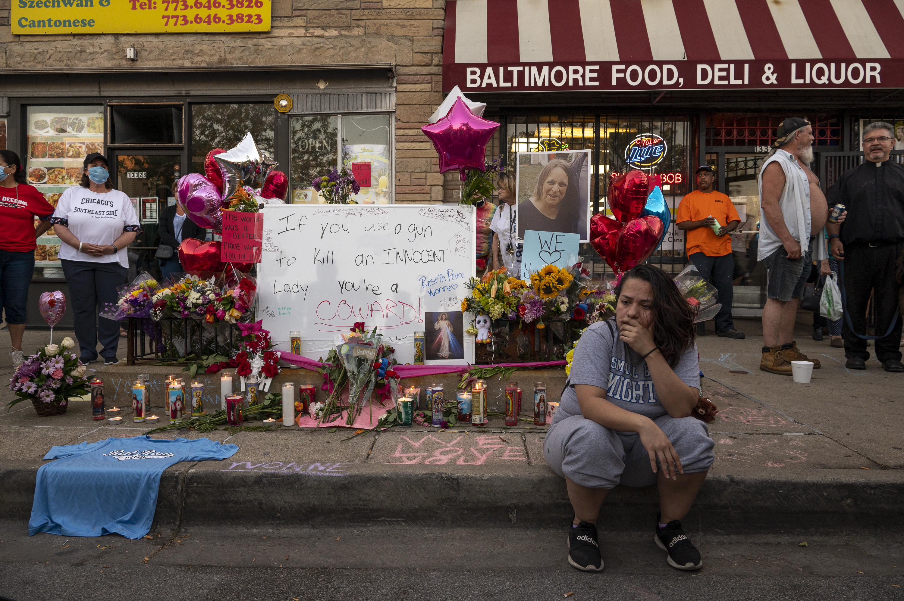 A woman sits in front of a memorial set up for Yvonne Ruzich outside Baltimore Food & Liquor Store in the Hegewisch neighborhood, Monday, Aug. 16, 2021.