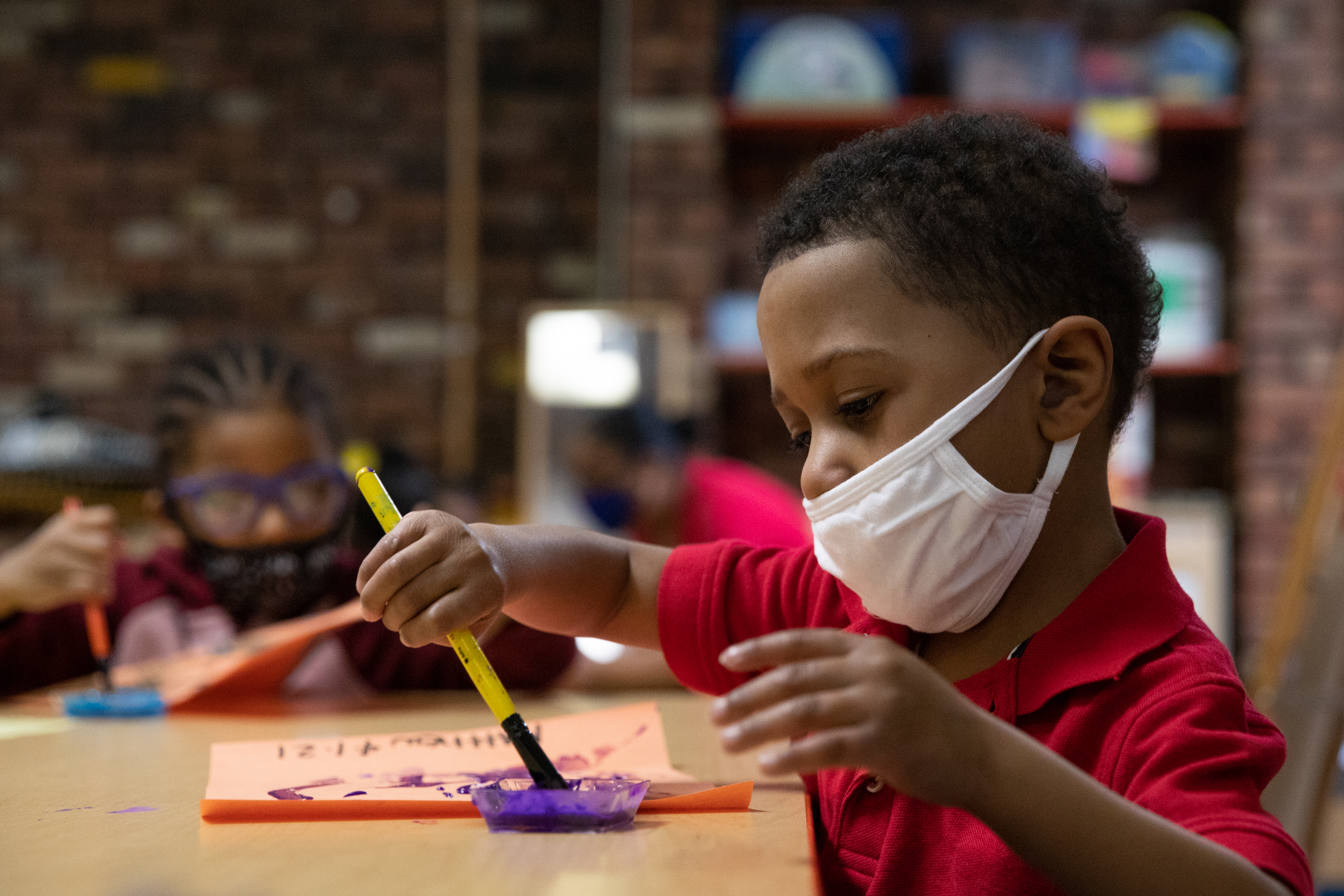 A young boy sitting in front of a piece of paper dips his brush in paint while at a preschool class.