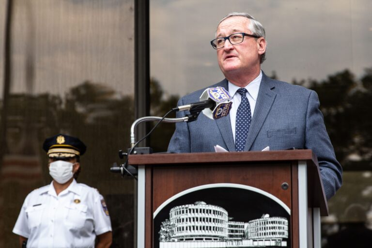 Philadelphia Mayor Jim Kenney speaks at a podium in front of glass windows, as a police officer wears a dress uniform and protective mask behind him.