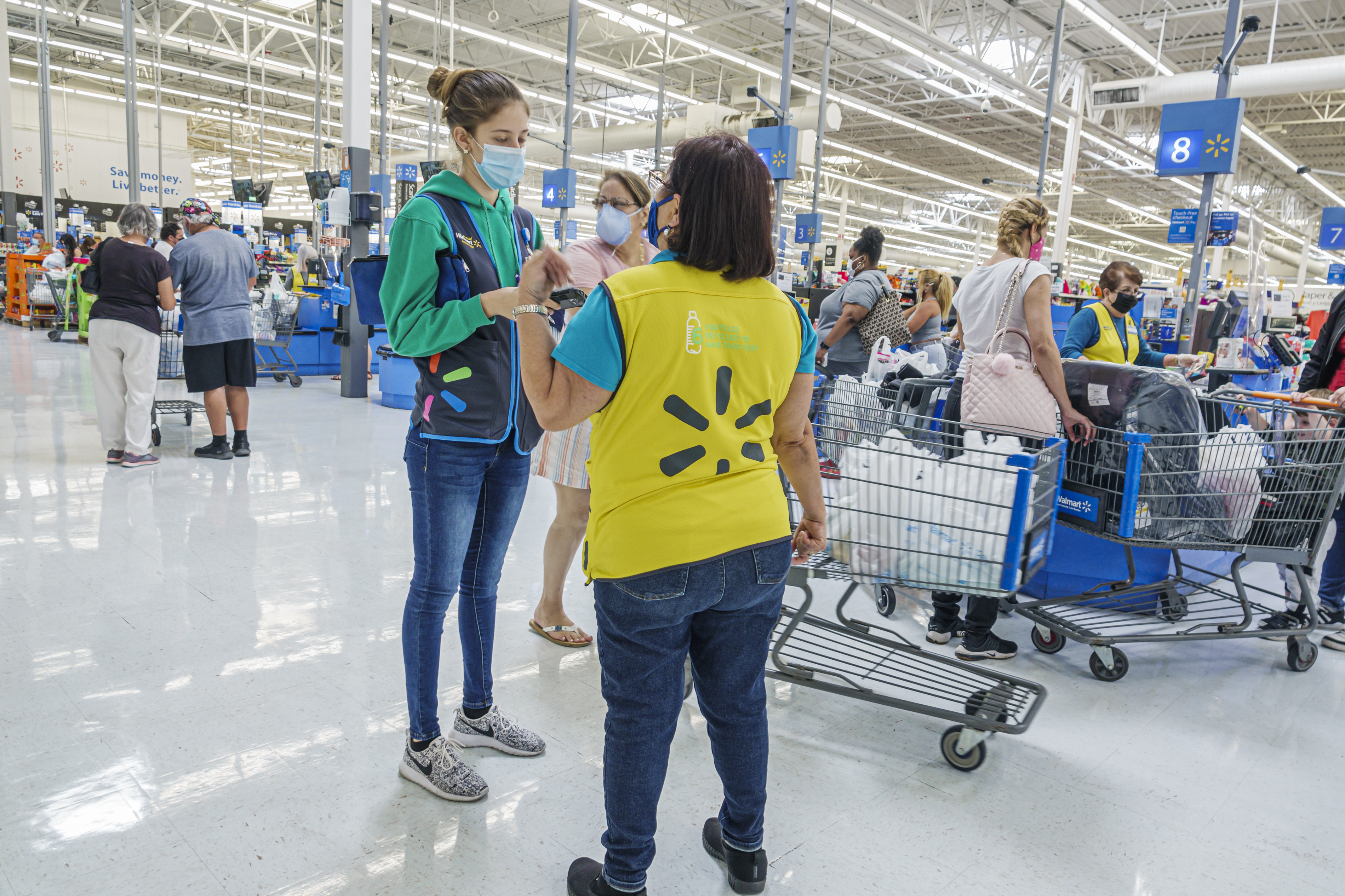 Two Walmart workers in masks talk to each other near a checkout line.