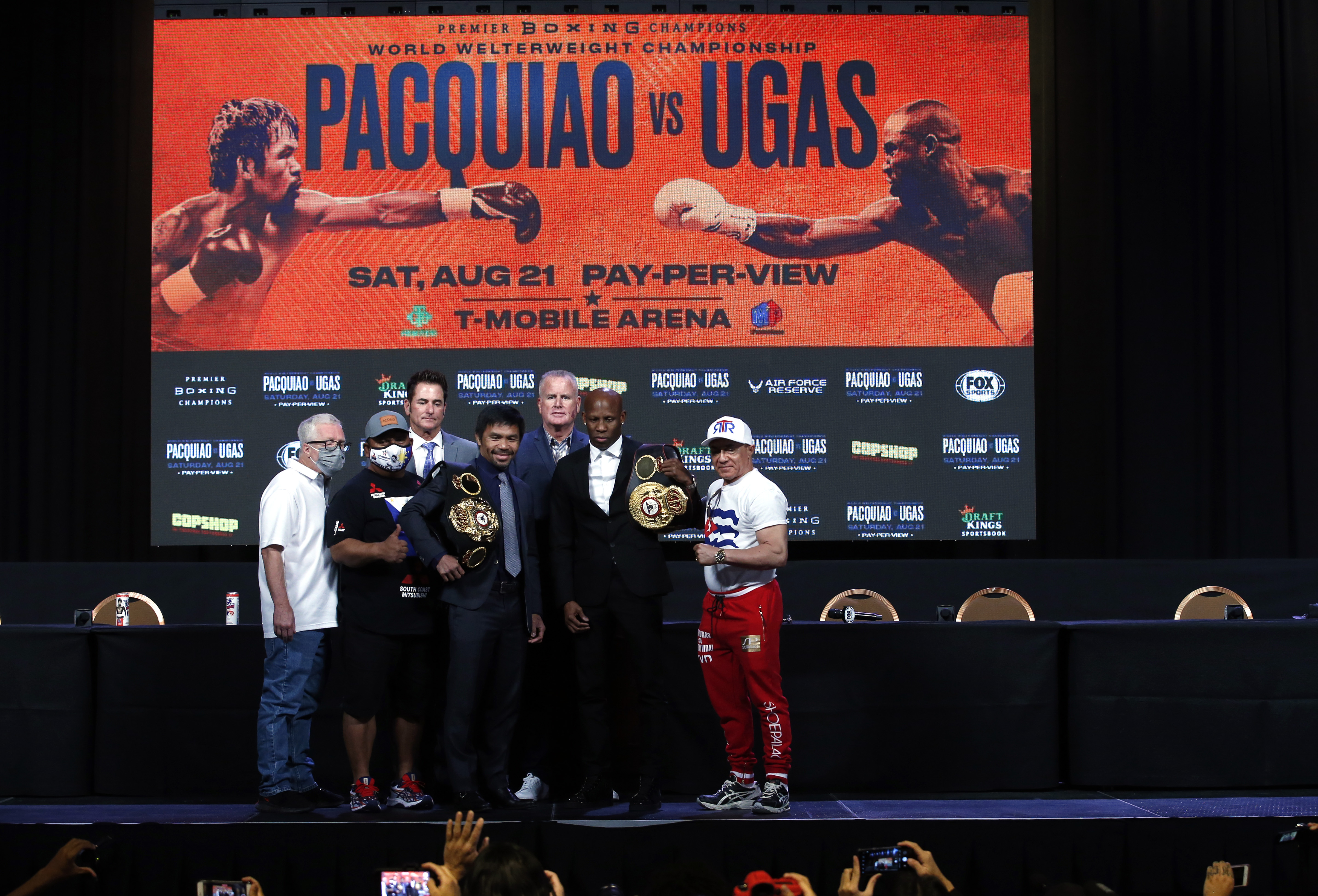 Manny Pacquiao (L) and WBA welterweight champion Yordenis Ugas pose with trainers and members of their teams during a news conference at MGM Grand Garden Arena on August 18, 2021 in Las Vegas, Nevada.