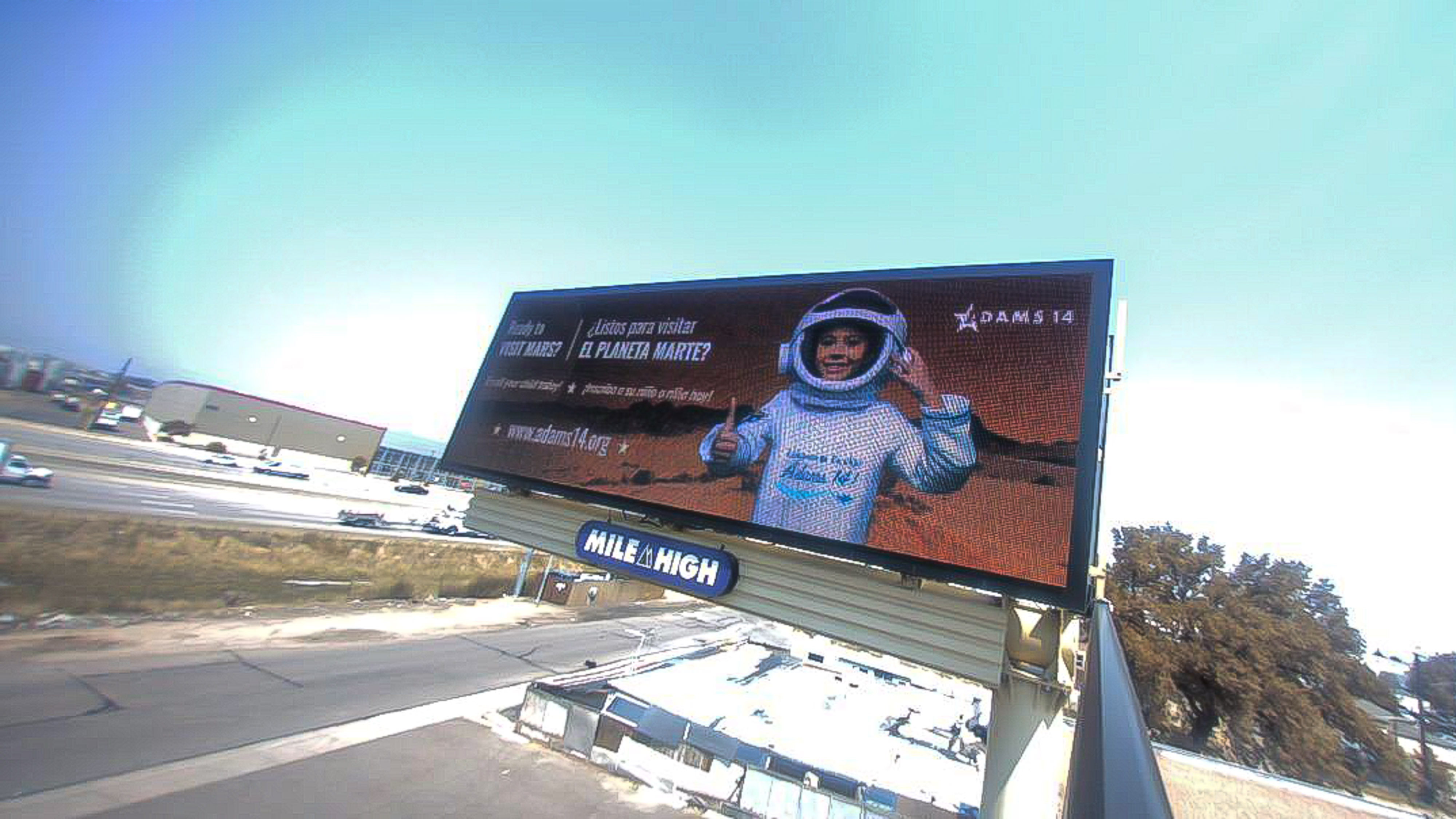 """A billboard for Adams 14 School District shows a child as an astronaut with the text """"Ready to visit Mars?"""" on the left-hand side in English and Spanish."""