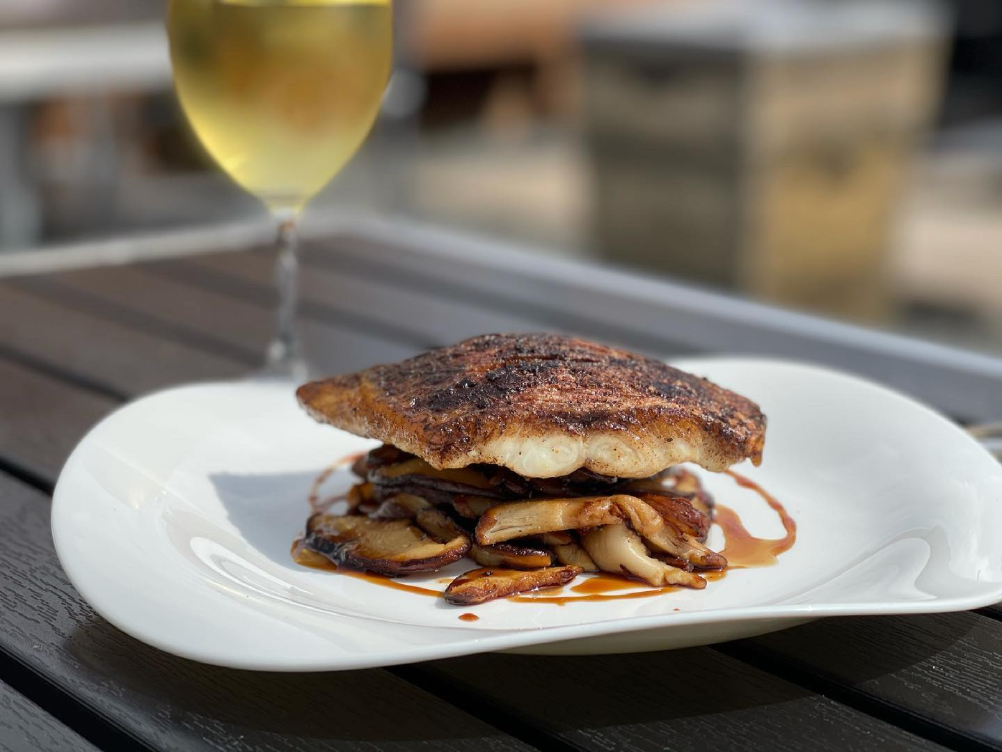 a plank of seared snapper on a bed of sauteed mushrooms