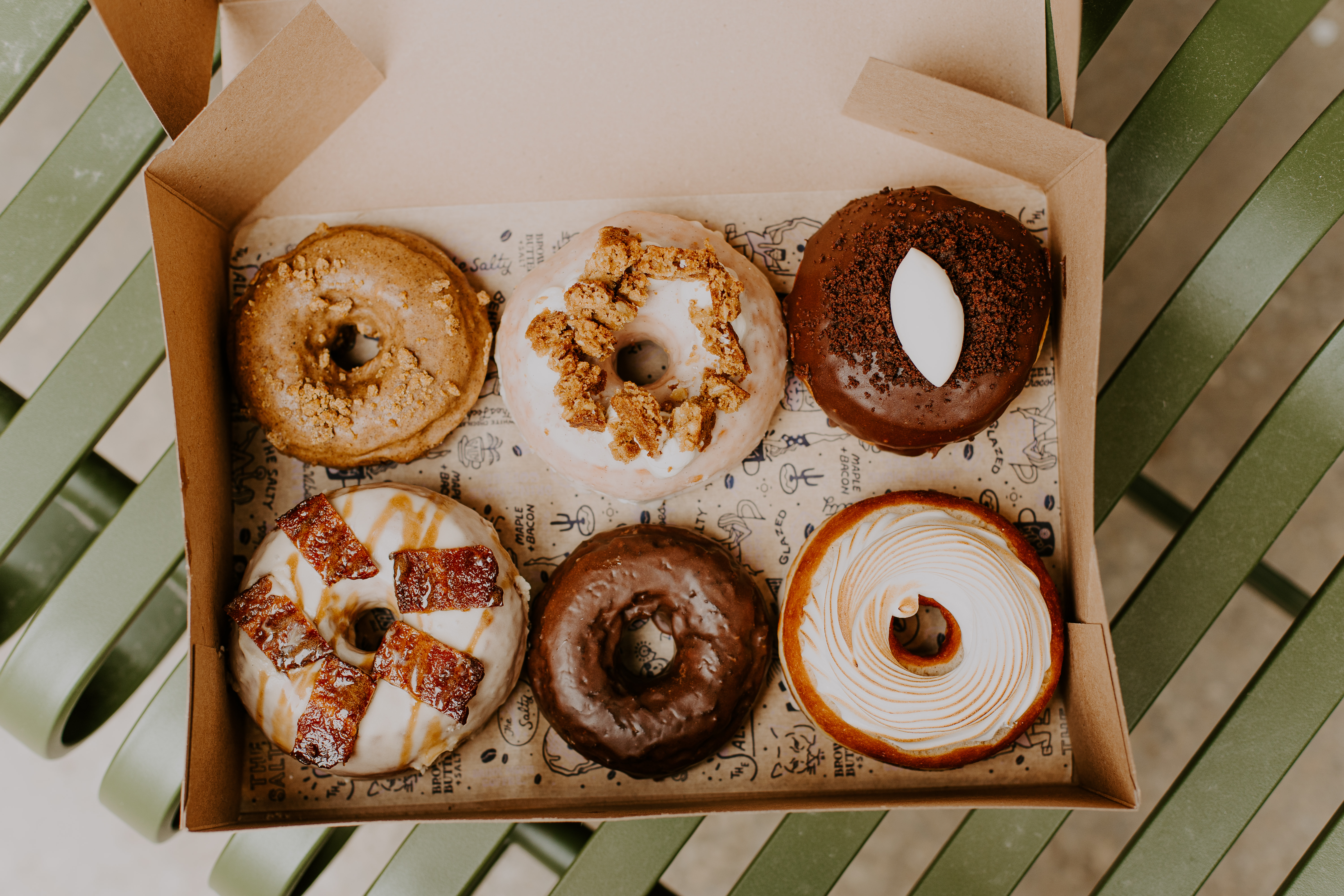 A box of doughnuts, some covered in chocolate, others topped with bacon or cookies