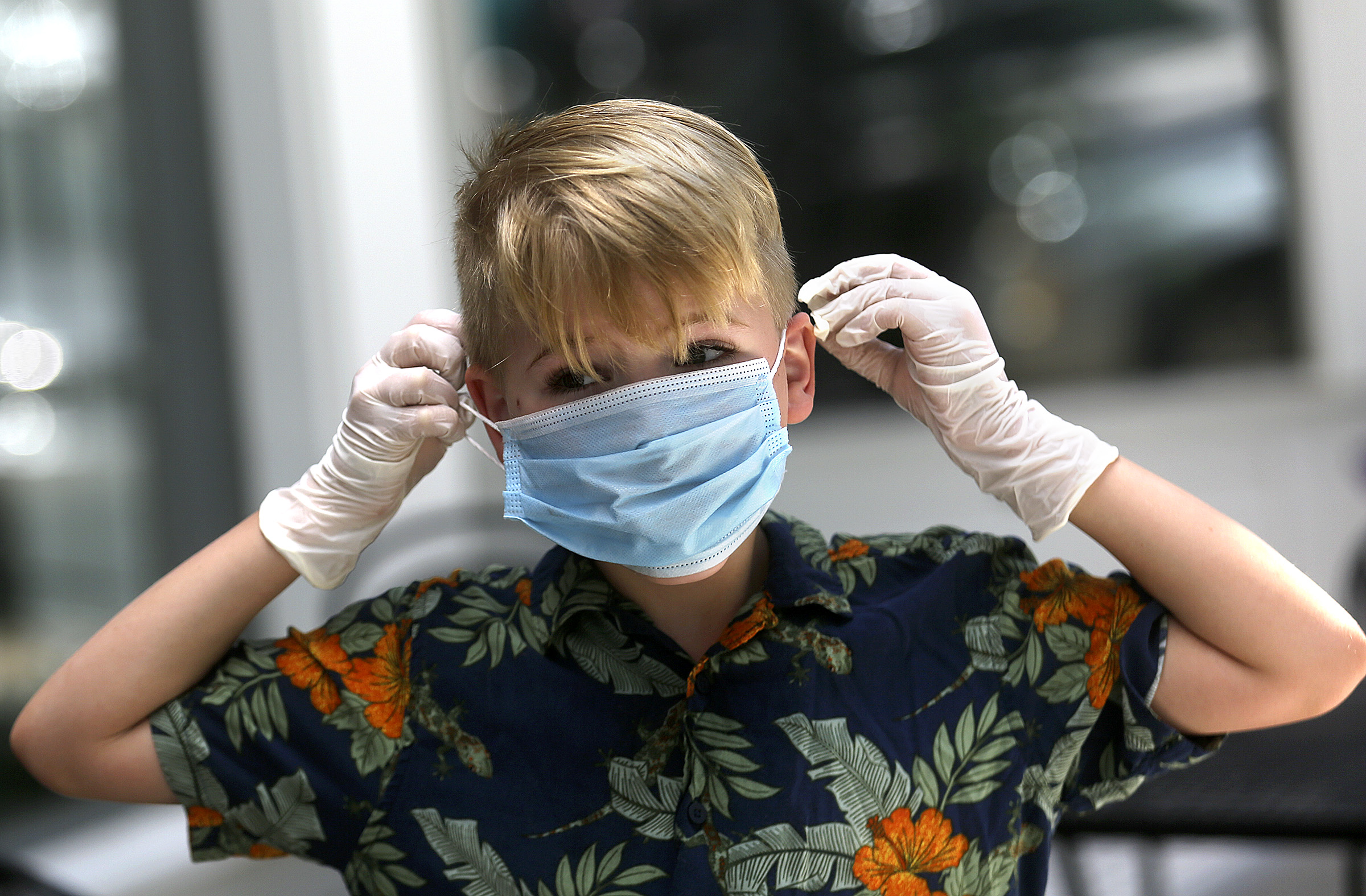 Barret Pritchard, 8, puts on a mask while working at a lemonade stand with his sister in Provo.