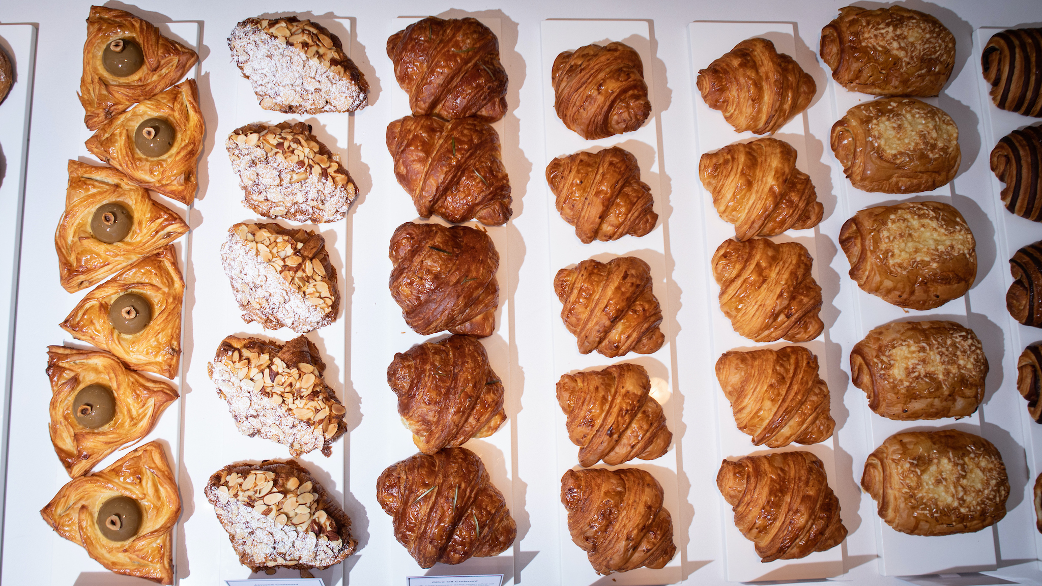 An overhead shot of a spread of croissants and other pastries lined up by type on white butcher paper.