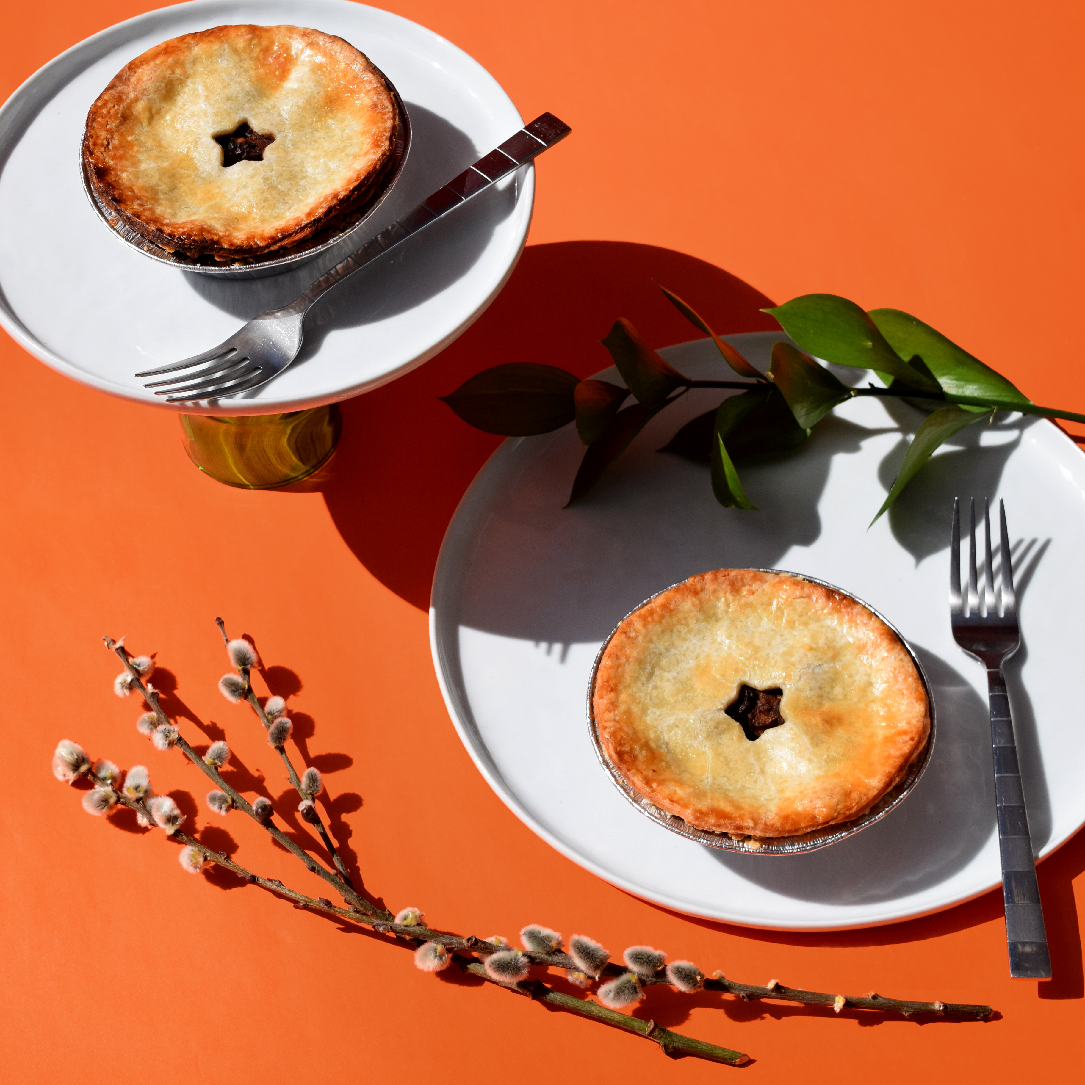 Two pot pies sit on plates on an orange table. The pies were made by Alexandria Guevarra of Allie G's Pastries, the Portland-based Filipino American pop-up known for its savory and sweet Filipino baked goods.