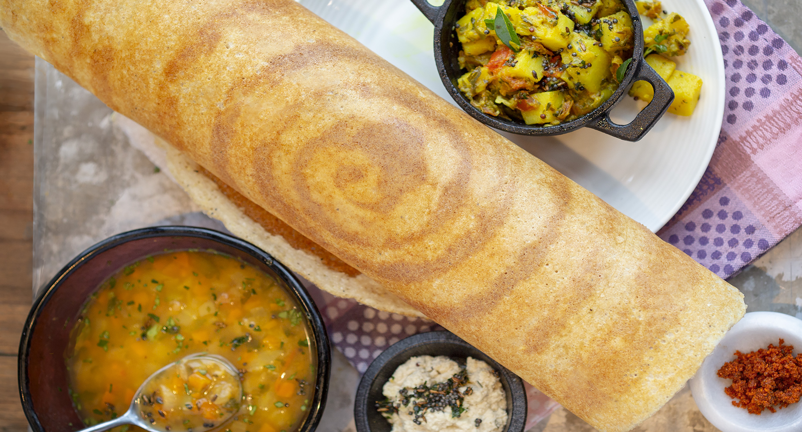 A plate with a dosa, sambar, and more.