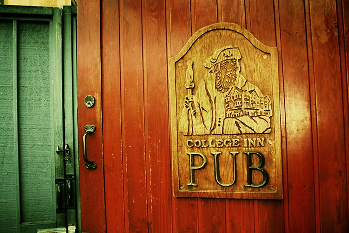 A wood door with a golden embossed sign that says the College Inn Pub with an engraved visage of a scholar and a green door to the left.