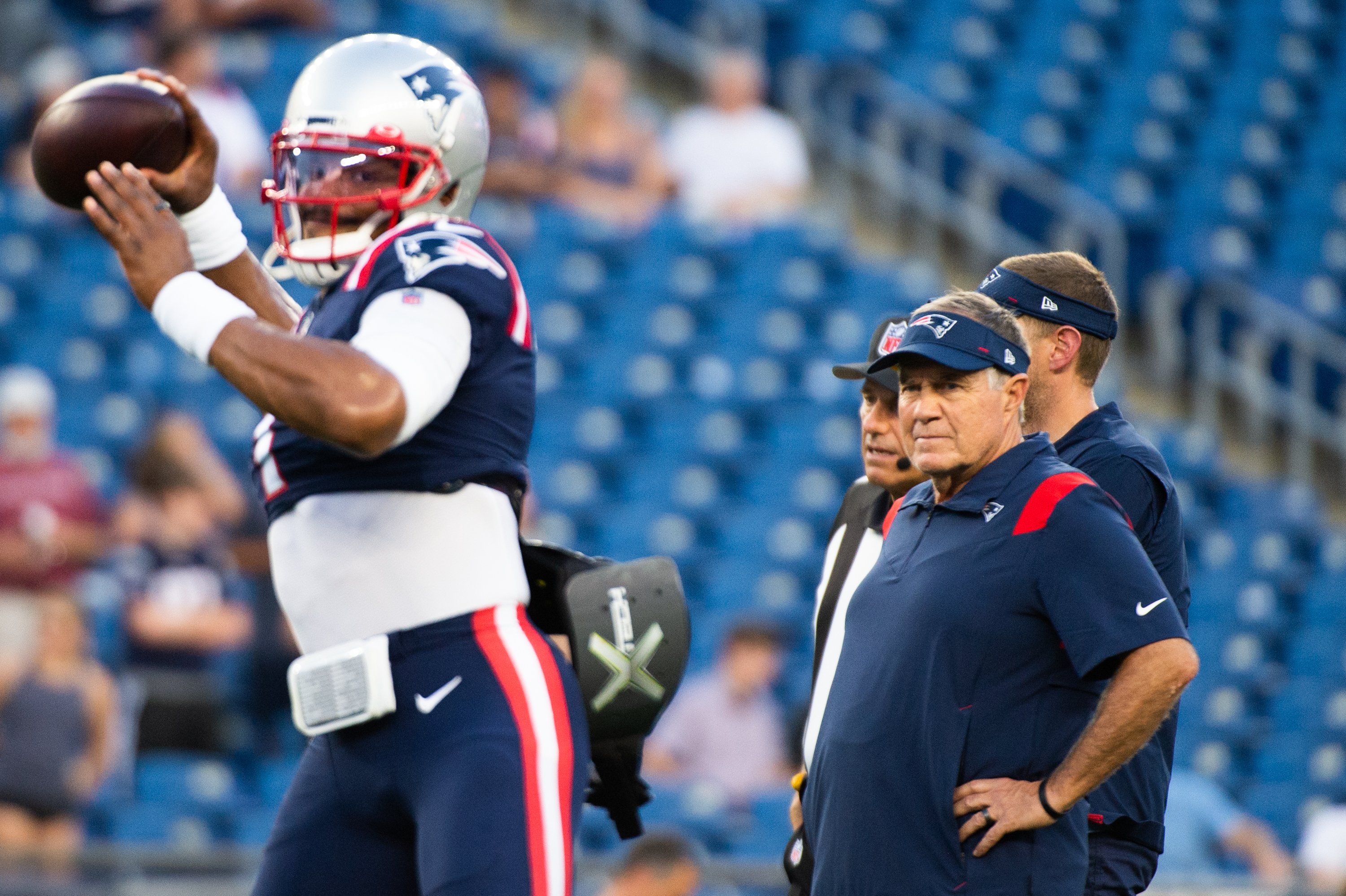 New England Patriots head coach Bill Belichick watches Cam Newton #1 during warm ups prior to the start of the game against the Washington Football Team at Gillette Stadium on August 12, 2021 in Foxborough, Massachusetts.