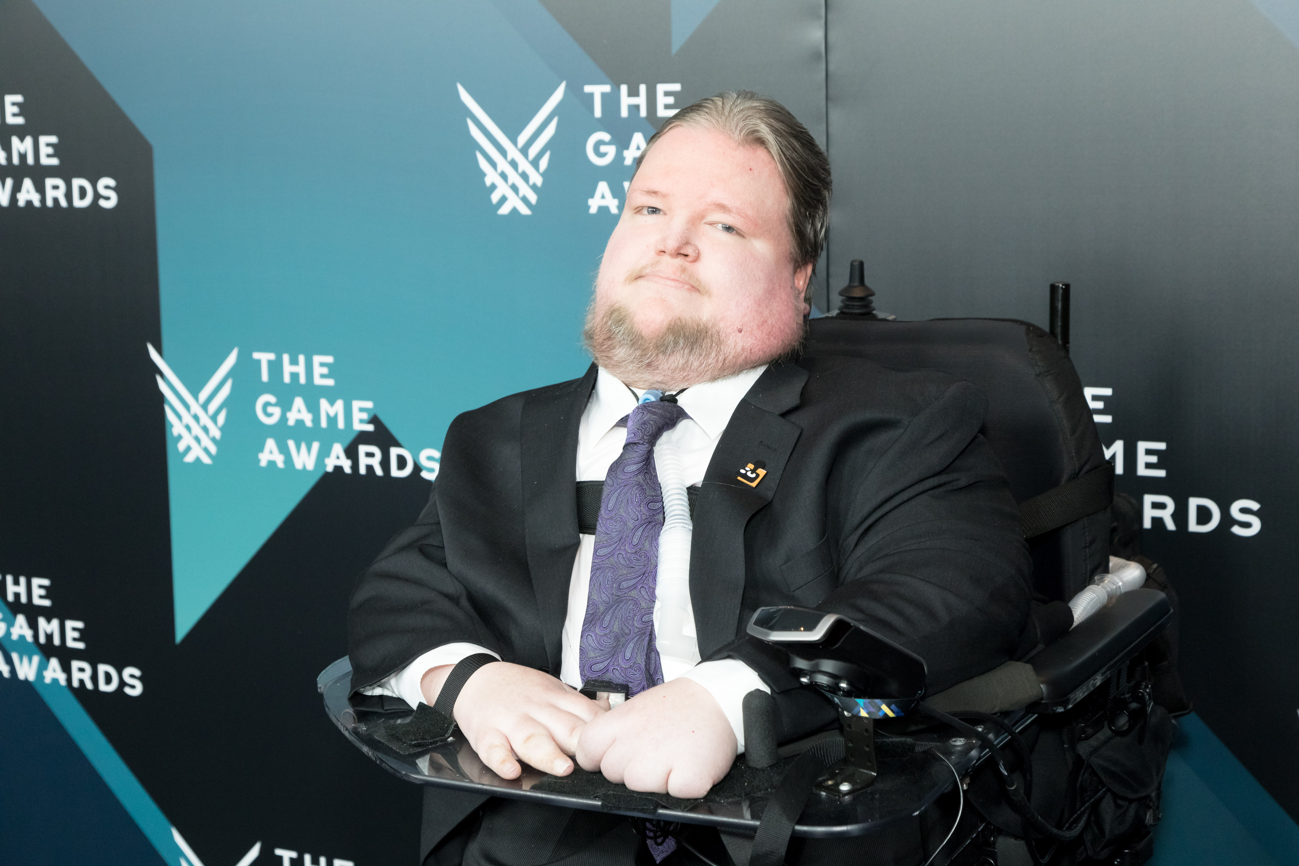 """Steven Spohn wearing a suit, sitting in his wheelchair in front of a backdrop with """"The Game Awards"""" on it."""