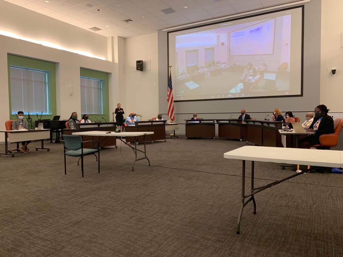 Board of Education meeting inside the meeting hall of the School District of Philadelphia's headquarters. Participants are socially distanced and the foreground shows a lot of empty carpeted area.