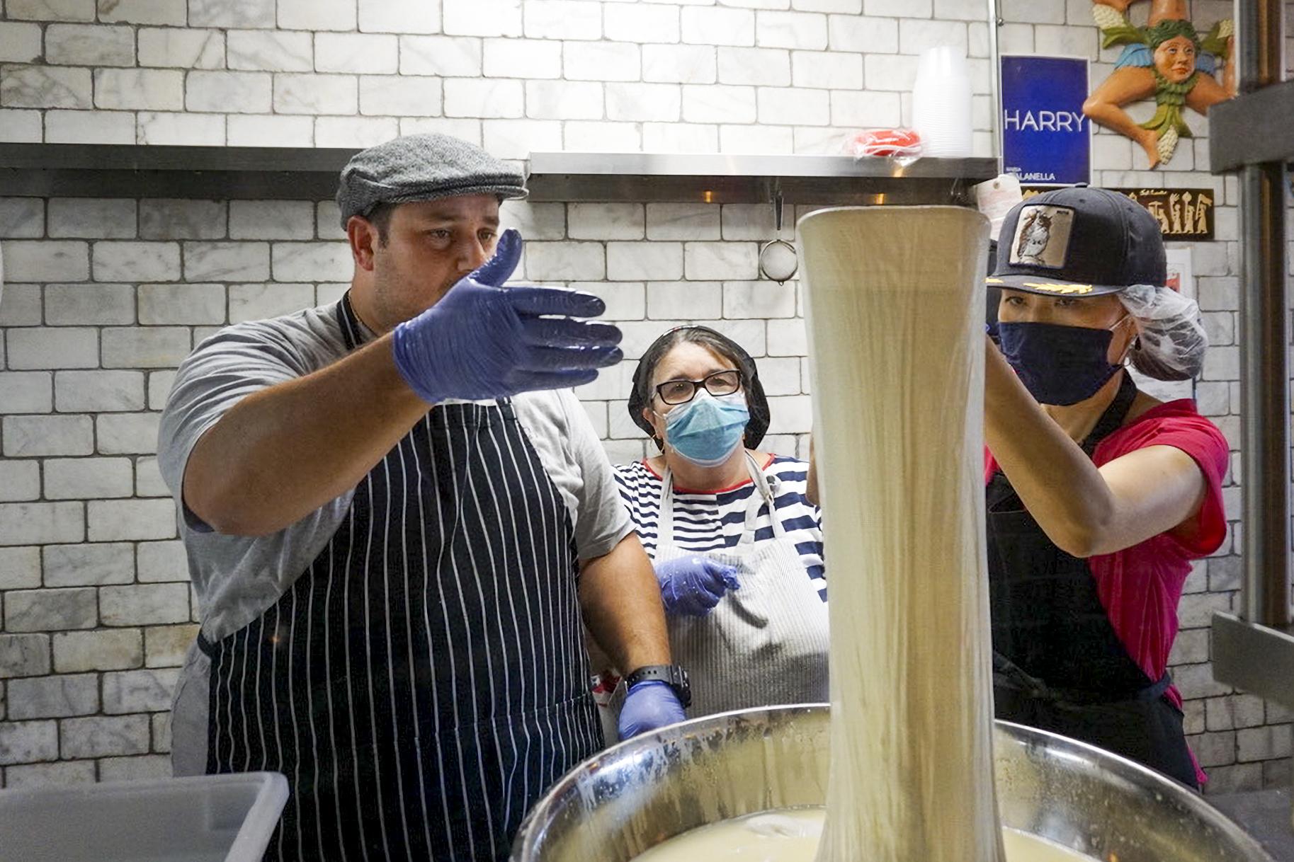 Nonnas Adelina Orazzo, center, and Yumi Komatsudaira, right, make fresh mozzarella with vendor Anthony Agostino on Thursday ahead of Enoteca Maria's grand reopening.