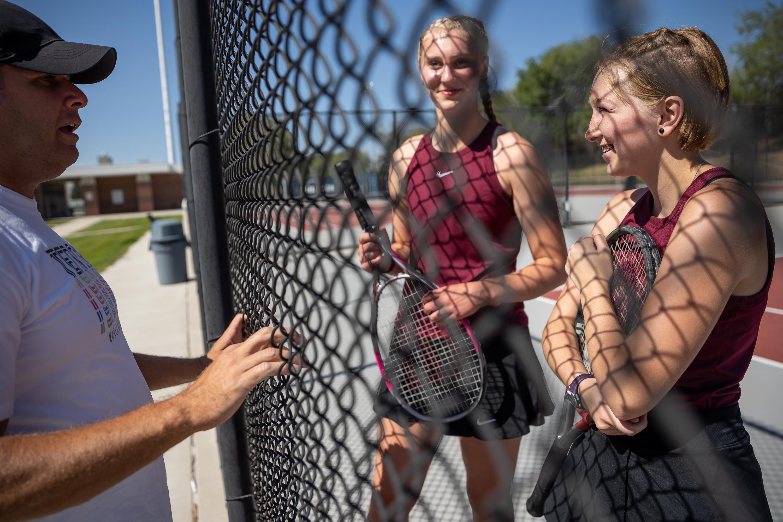 Matt Bell, coach for Jordan High School girls tennis, talks to Gretchen Baum and Jolie Sealey during their match at the school in Sandy on Wednesday, Aug. 11, 2021.