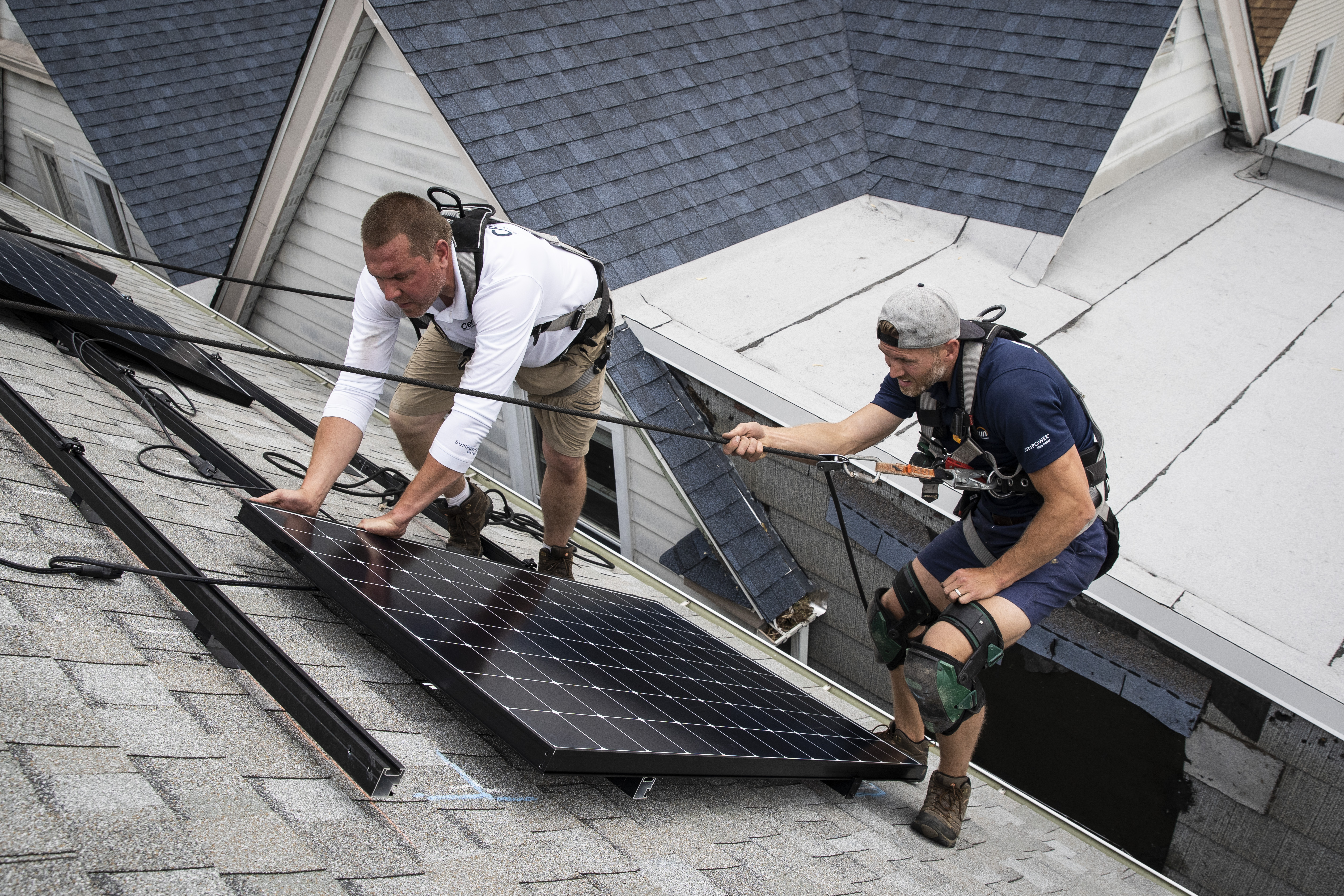 Pete Southerton (left) and Tom Bradshaw of solar energy contractor Certasun installing solar panels on a Northwest Side home in May. The Buffalo Grove company has seen business decline by half as consumers are unable to tap state incentives.
