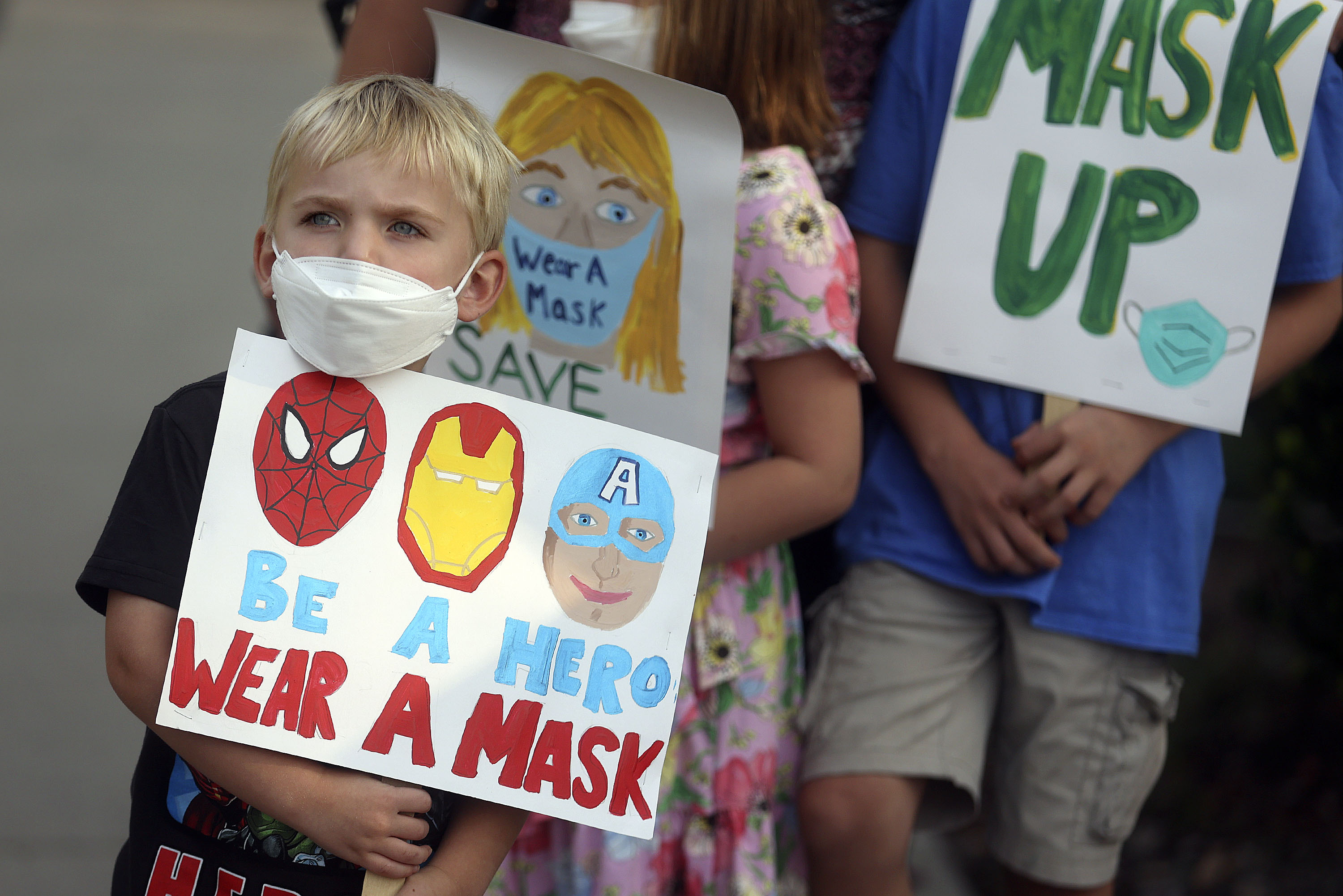 David Phillips holds a sign in support of school mask mandates.