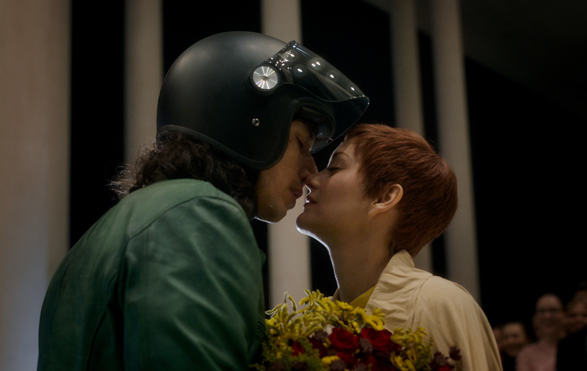 A man and a woman lean in for a kiss.