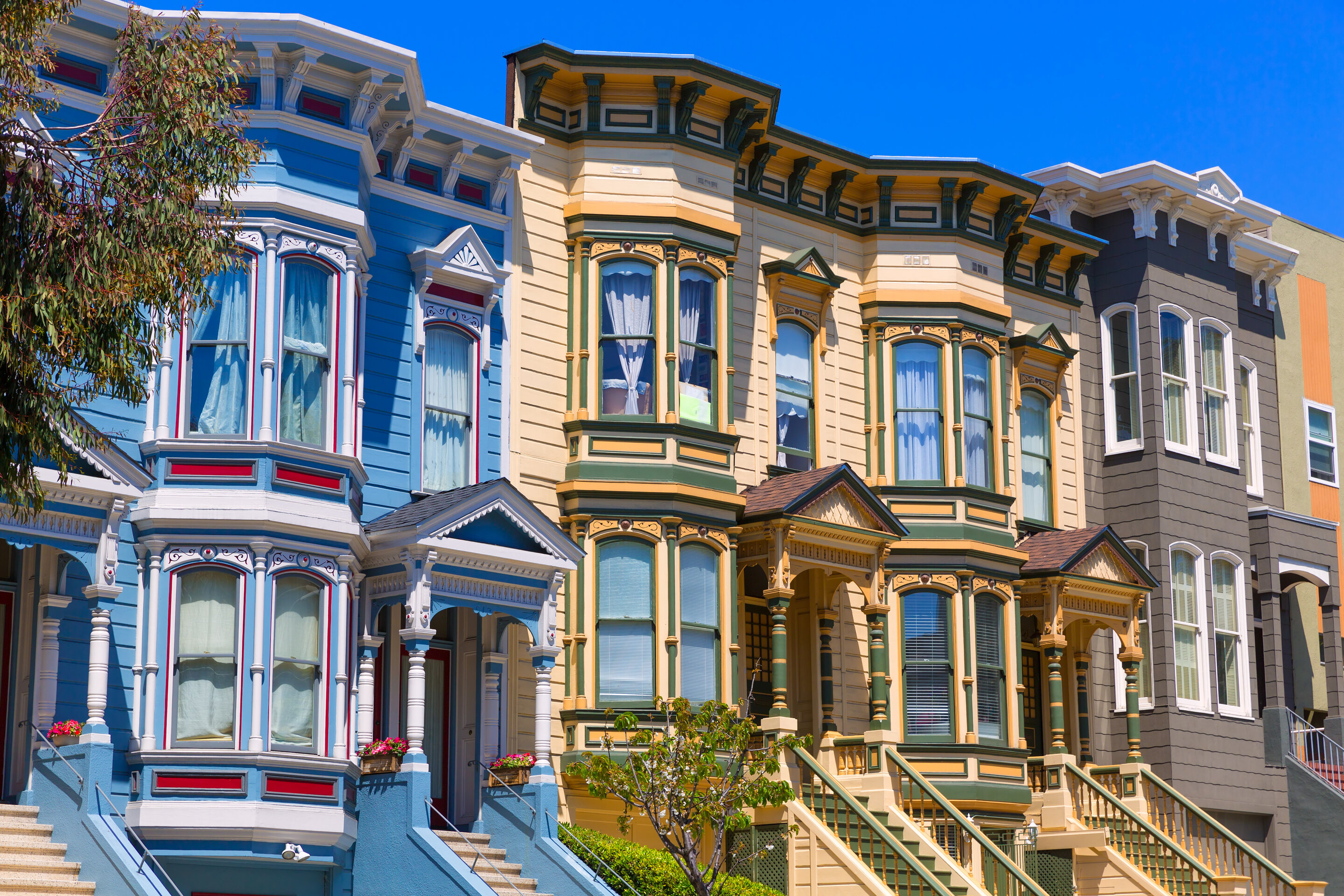 Colorful row homes in San Francisco, California painted yellow, blue, and brown.